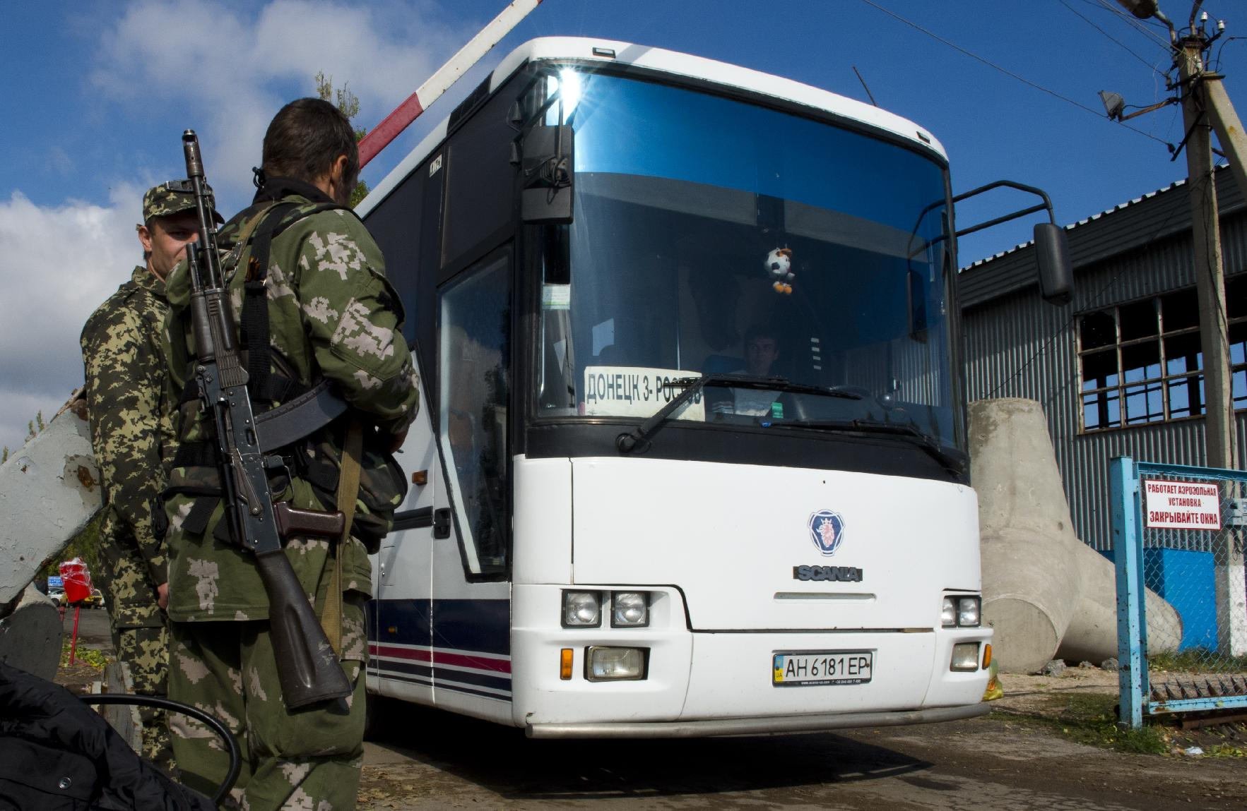 Pro-Russian separatist border guards let a bus crossing from Ukraine to Russia at the Uspenka border post, on September 26, 2014.