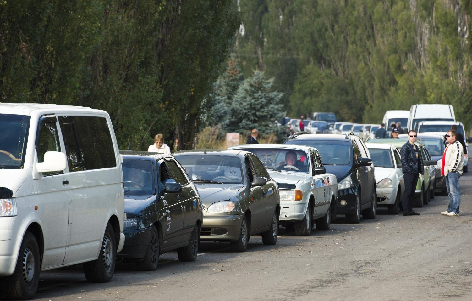 People queue up to cross from Ukraine to Russia at the Uspenka border post, held by pro-Russian separatists, on September 26, 2014.