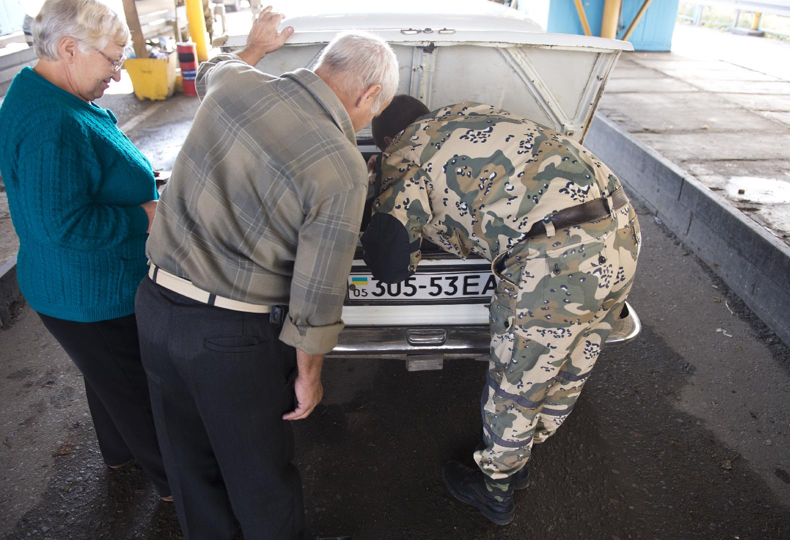 A pro-Russian separatist border guard searches a car on September 26, 2014 on its way from Ukraine to Russia at the Uspenka border post, held by separatists from the self-proclaimed People's Republic of Donetsk.