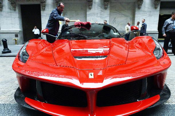 An employee shines a Ferrari displayed in front of the New York Stock Exchange on October 13, 2014