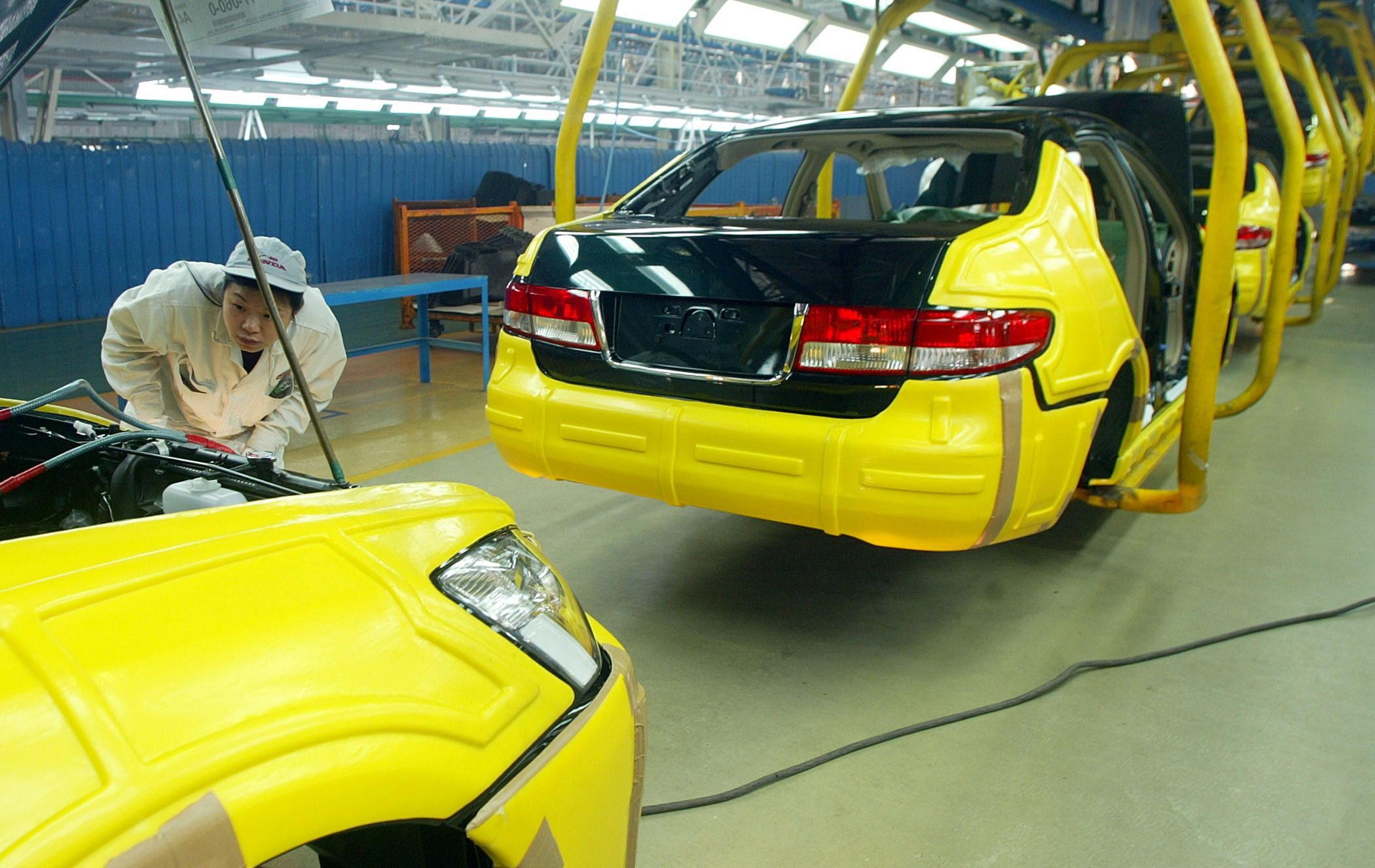 A worker inspects a Honda Accord car model at the Honda assembly plant in the southern Chinese city of Guangzhou, on January 17, 2003