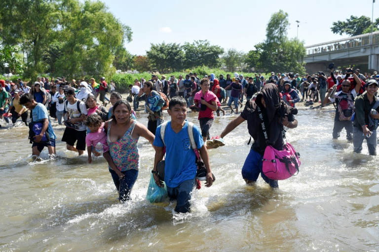 Troops fire gas as migrants try to storm into Mexico