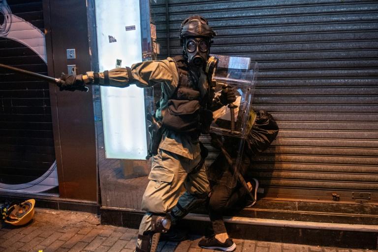 Hong Kong lashed by fresh violence as thousands defy mask ban