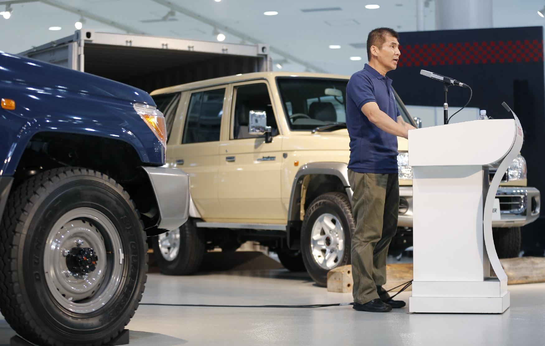 Toyota Land Cruiser chief engineer Sadayoshi Koyari speaks in front of the Land Cruiser 70 van, right, and its pickup model, left, during the Land Cruiser Motor Show at a Toyota showroom in Tokyo Monday, Aug. 25, 2014. Toyota Motor Corp. is bringing back the Land Cruiser 70 in Japan, catering to nostalgic demand for the rugged off-road vehicle. The Land Cruiser 70, the toughest of the Land Cruiser models, arrives at Japanese dealers Monday. But it's on sale for only a year. (AP Photo/Shizuo Kambayashi)
