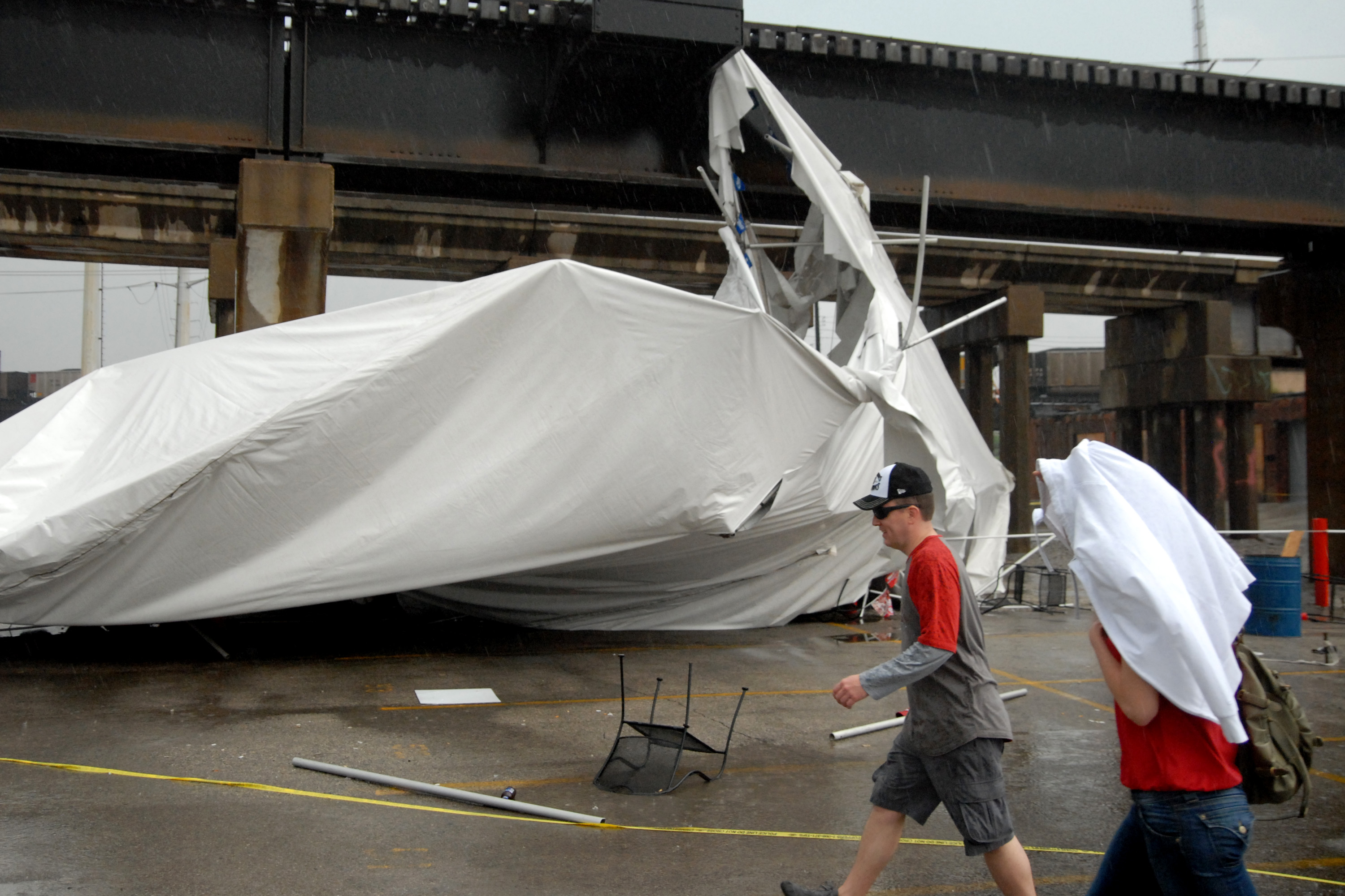 A party tent from Kilroy's Sports Bar in St. Louis rests against a railroad trestle near the bar after storm winds blew through the area following a baseball game between the St. Louis Cardinals and Milwaukee Brewers at nearby Busch Stadium Saturday, April 28, 2012. One person died Saturday and more than a dozen were taken to a hospital with injuries after high winds blew over a beer tent near Busch Stadium in St. Louis. (AP Photo/Sid Hastings)