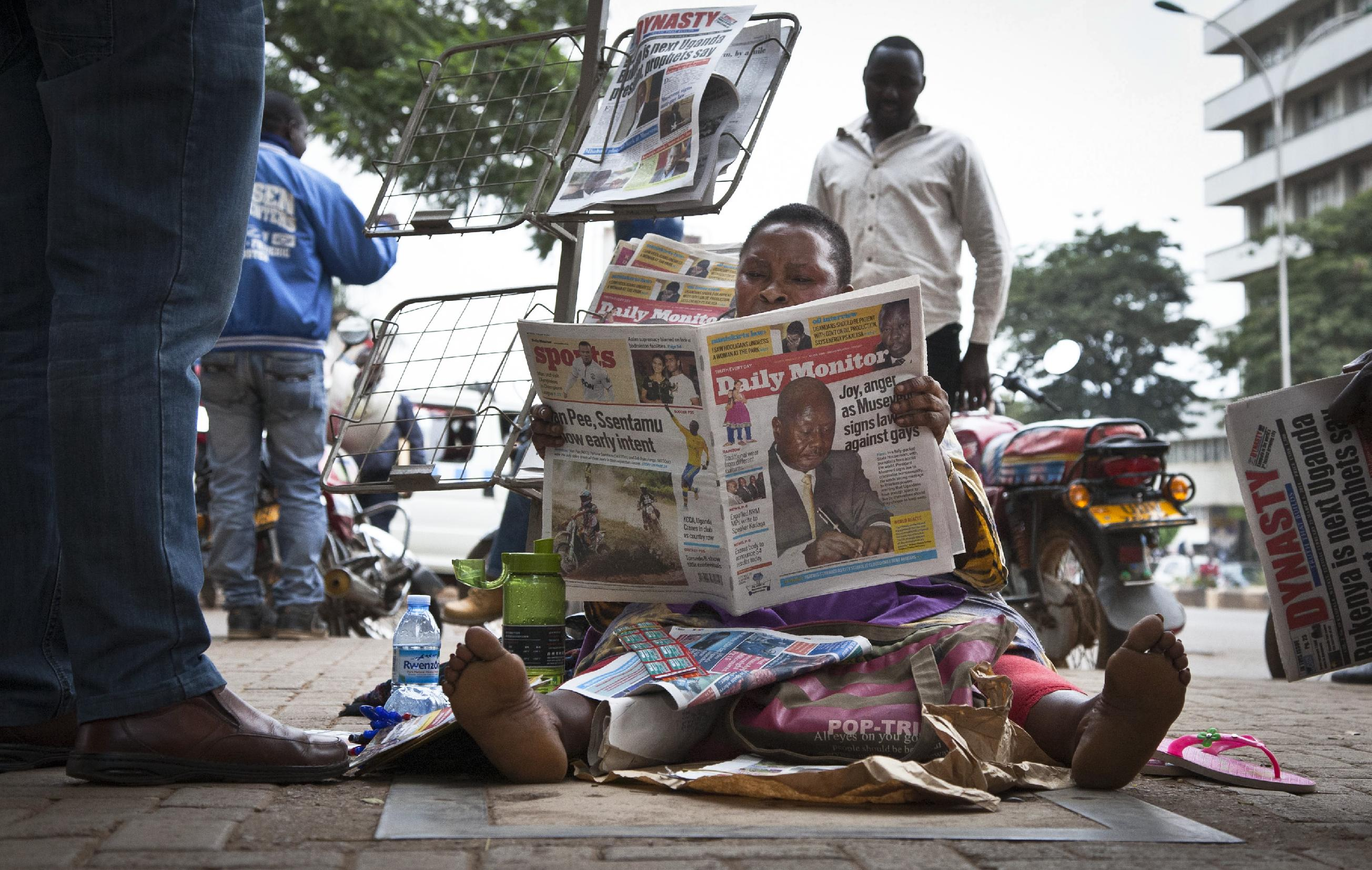 """A Ugandan newspaper seller reads a copy of the """"Daily Monitor"""" newspaper on the street in Kampala, Uganda Tuesday, Feb. 25, 2014. The Ugandan """"Red Pepper"""" tabloid newspaper published a list Tuesday of what it called the country's """"200 top"""" homosexuals, outing some Ugandans who previously had not identified themselves as gay, one day after the president Yoweri Museveni enacted a harsh anti-gay law. (AP Photo/Rebecca Vassie)"""