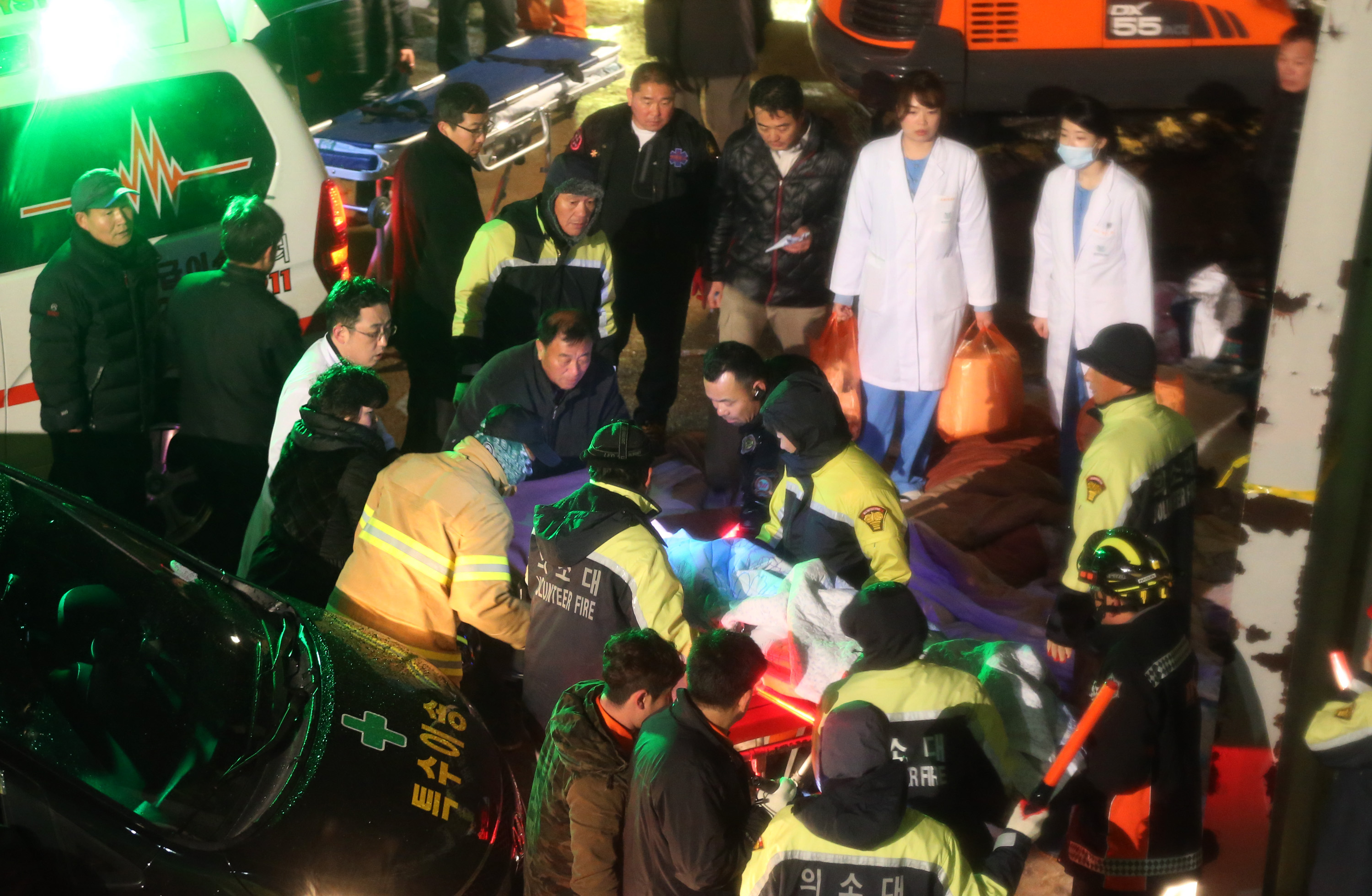 Rescue workers carry a victim, medical condition unknown, from a collapsed resort building in Gyeongju, South Korea, Monday, Feb. 17, 2014. South Korean police and news reports say that dozens of university students are feared trapped after a building's roof collapsed because of recent heavy snowfall. (AP Photo/Yonhap, Lee Sang-hyun) Korea Out