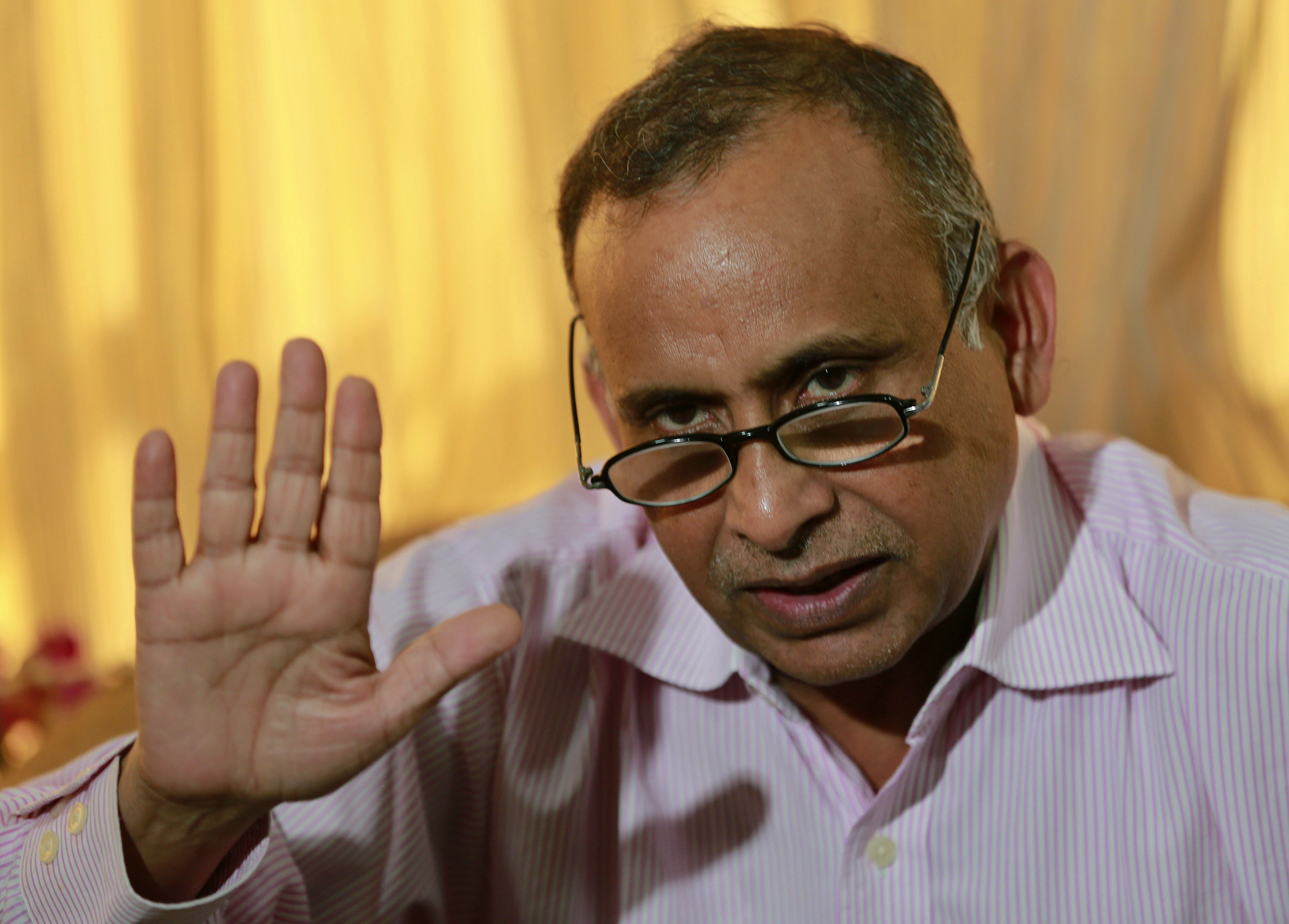 Uttam Khobragade, father of Indian diplomat Devyani Khobragade, who was arrested and strip-searched in New York, gestures as he speaks at a press conference in Mumbai, India, Thursday, Dec. 19, 2013. The case has sparked a diplomatic furor between the United States and India, which is incensed over what its officials describe as degrading treatment of India's deputy consul general in New York. (AP Photo/Rafiq Maqbool)