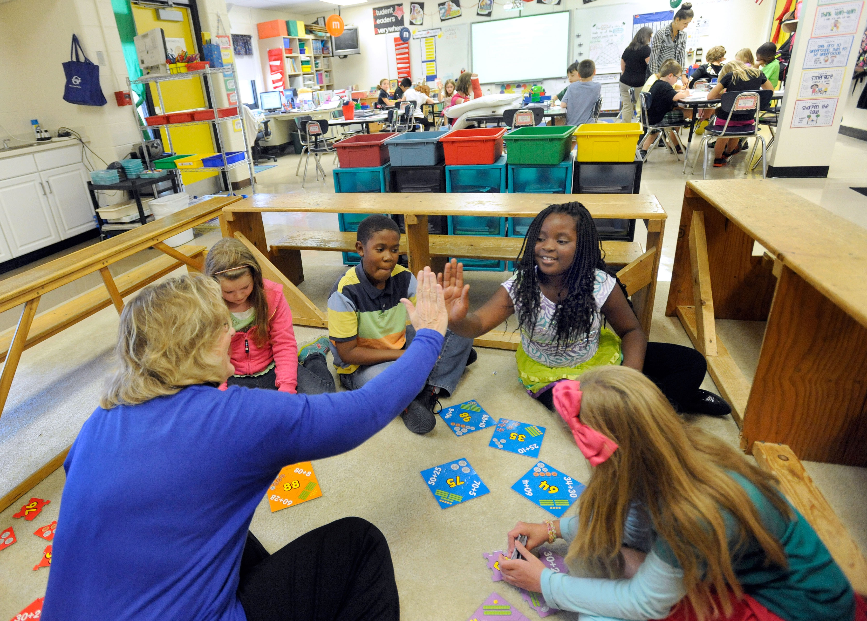Third-grade teacher Sherry Frangia, left, high-fives student Jayla Hopkins during a math lesson at Silver Lake Elementary School in Middletown, Del. Tuesday, Oct. 1, 2013. Silver Lake has begun implementing the national Common Core State Standards for academics. (AP Photo/Steve Ruark)
