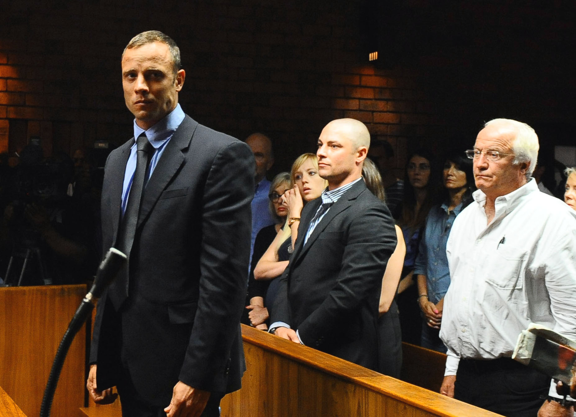 Oscar Pistorius, foreground, stands following his bail hearing, as his family looks on. (AP)