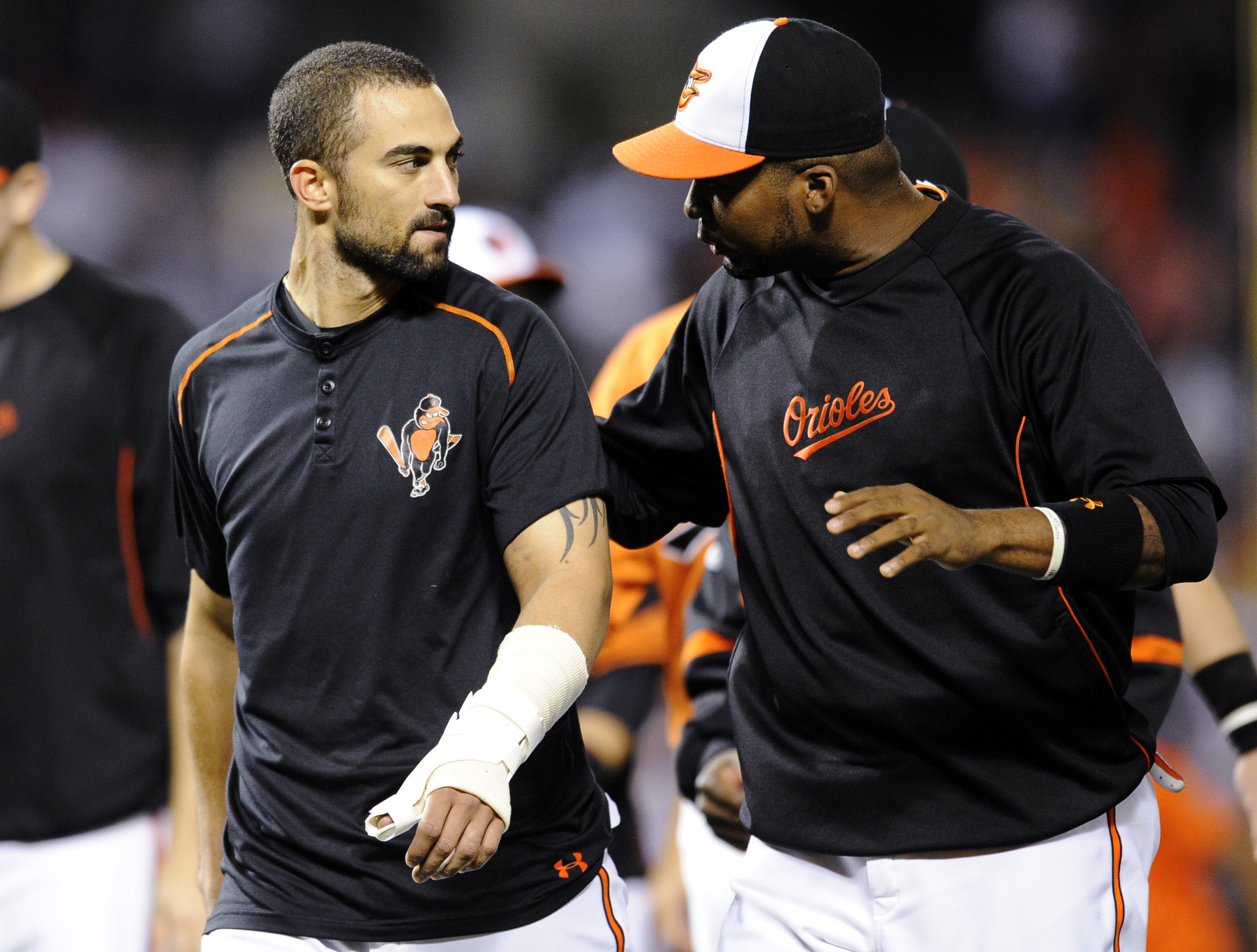 Nick Markakis, left, leaves the field with his thumb wrapped after celebrating the Baltimore's 5-4 win. (AP)