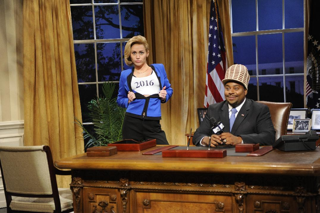 This Oct. 5, 2013 photo released by NBC shows guest host Miley Cyrus, left, and Kenan Thompson in a scene from the late-night comedy series 'Saturday Night Live,' in New York. (AP Photo/NBC, Dana Edelson)