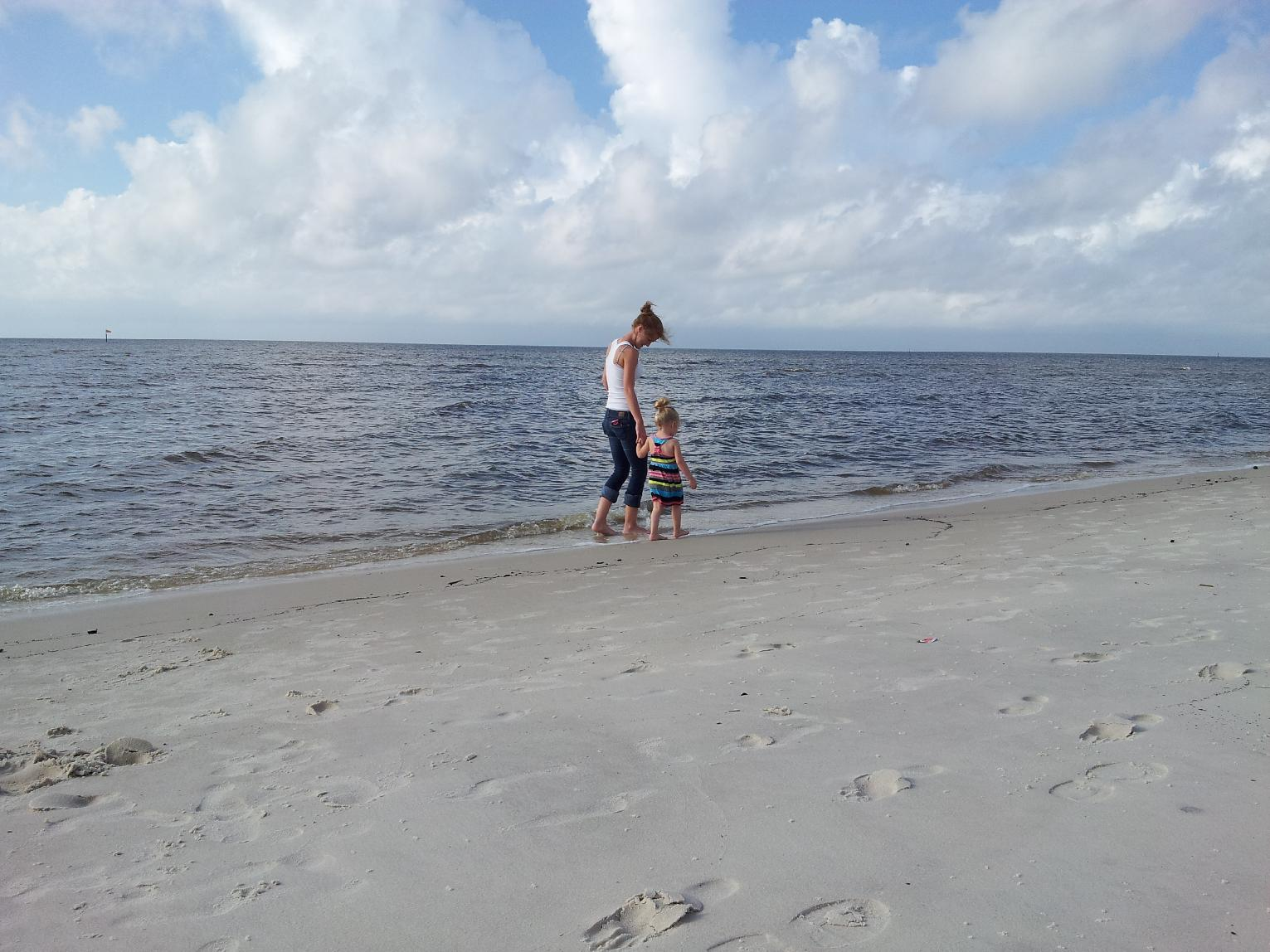 Robyn Comley, 19, and her 2-and-half-year-old niece, Teegan Greer, walk along the beach in Biloxi, Miss., on Saturday, Oct. 5, 2013. Tropical Storm Karen, though still churning in the Gulf of Mexico, weakened overnight. For the most part, it was business as usual on the Mississippi Gulf Coast (AP Photo/Holbrook Mohr)