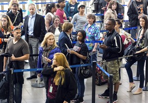 Travelers stand in line at Los Angeles International airport on Monday, April 22, 2013. (AP Photo/Damian Dovarganes)