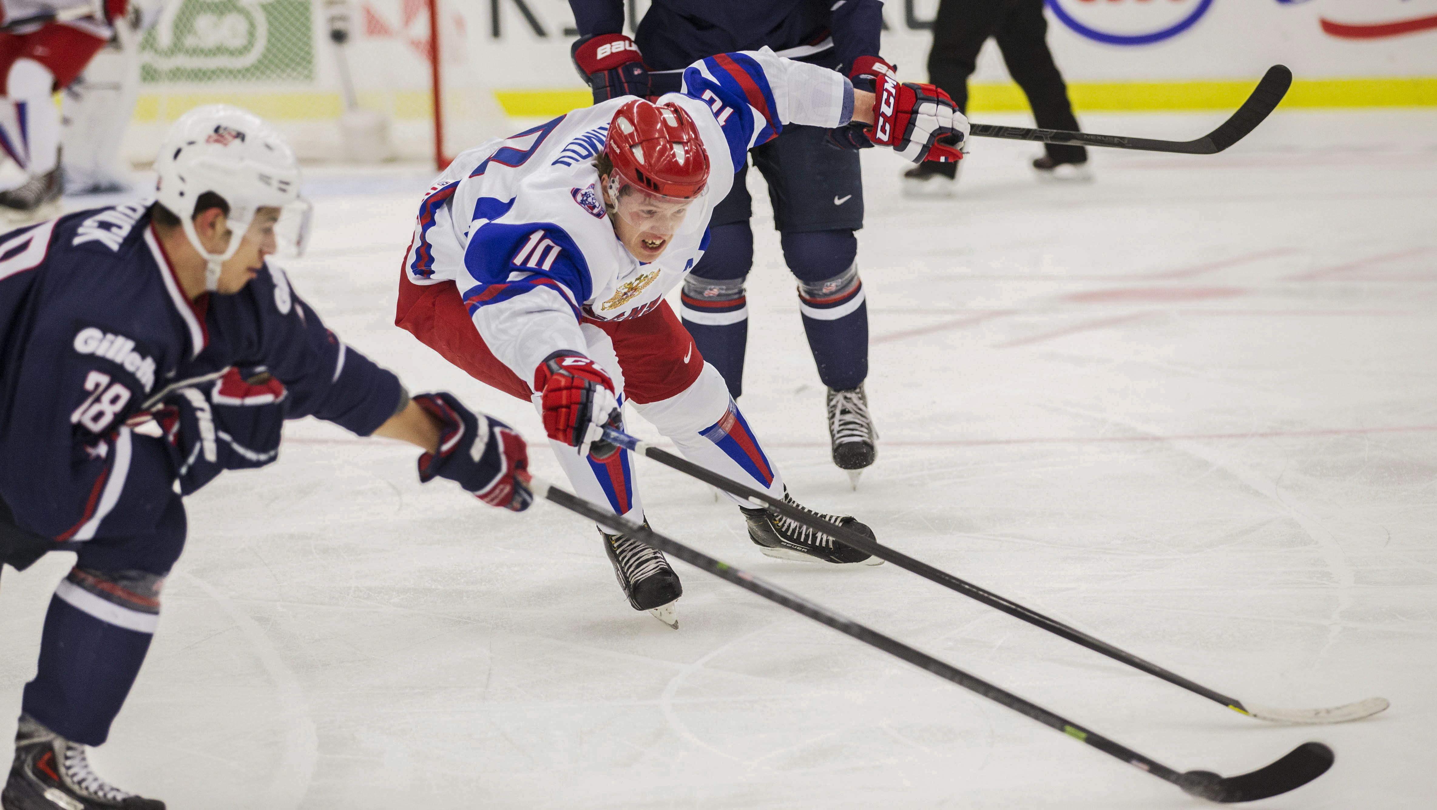 Russia's Bogdan Yakimov, center, fights for the puck with Connor Carrick of the USA during their World Junior Hockey Championships quarter final in Malmo, Sweden on Thursday, Jan. 2, 2014. (AP Photo/Andreas Hillergren) ** SWEDEN OUT **