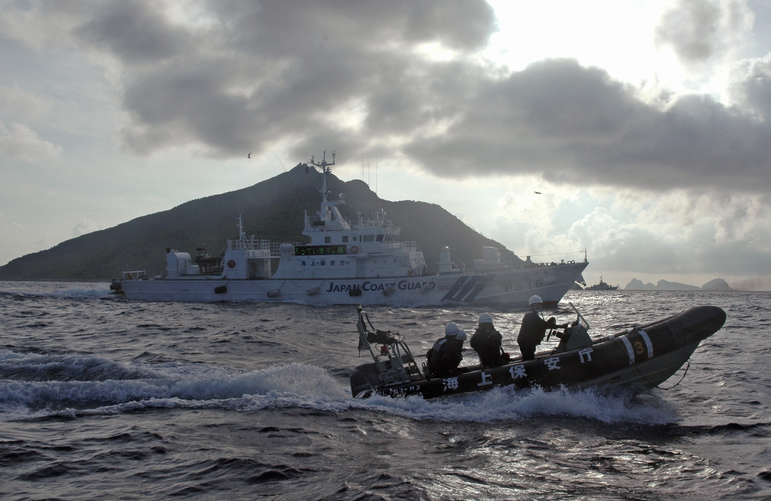 Japanese Coast Guard boat and vessel sail alongside Japanese activists' fishing boat, not in photo, warning the activists away from a group of disputed islands called Diaoyu by China and Senkaku by Japan, early Sunday, Aug. 18, 2013. Nearly two dozen Japanese nationalist activists and fishermen have sailed to a small group of islands at the center of a territorial dispute with China. They were closely monitored by Japan's Coast Guard, but there were no Chinese patrols in the area and no incidents were reported. (AP Photo/Emily Wang)