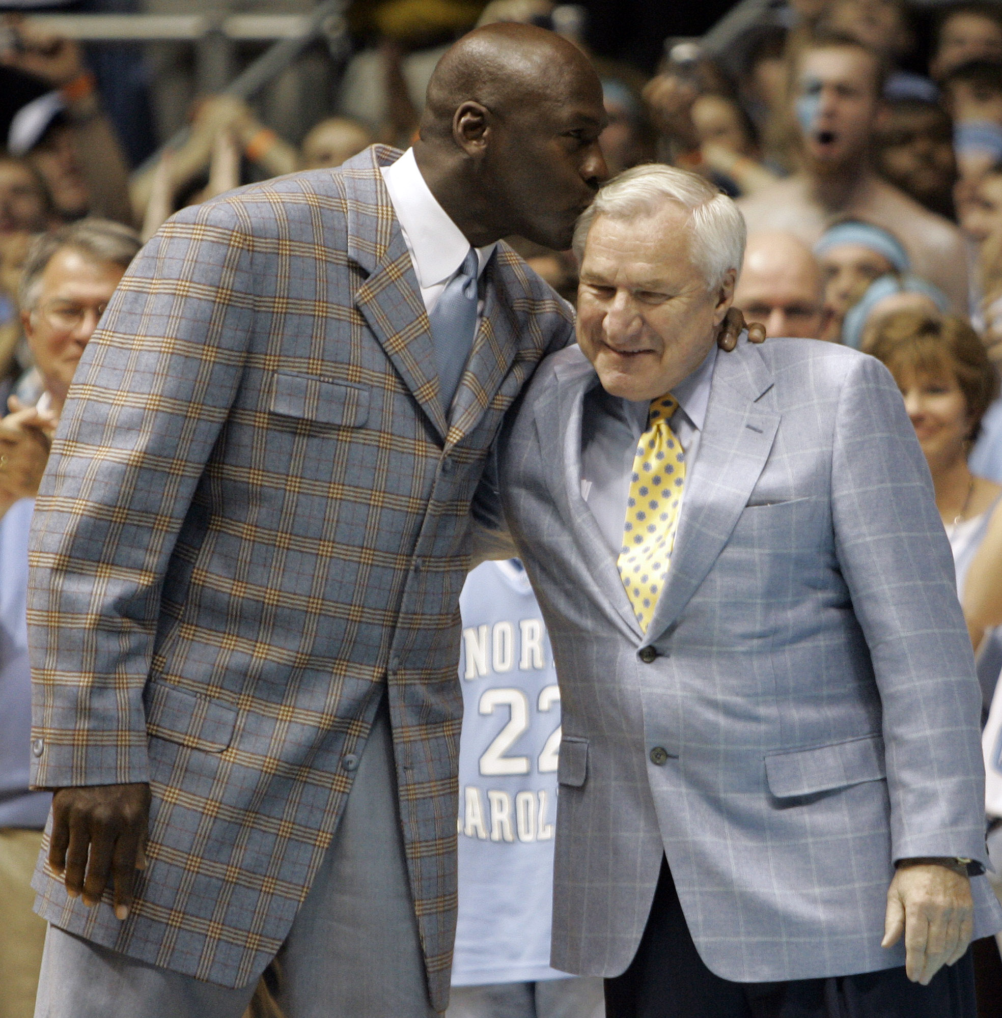 File-This Feb. 10, 2007, file photo shows former North Carolina player Michael Jordan, left, giving his former coach Dean Smith a kiss during halftime of a college basketball game between North Carolina and Wake Forest in Chapel Hill, N.C. ``It's a whole new world,'' said Steve Fisher, the 70-year-old San Diego State coach who made his name leading Michigan's Fab Five to the Final Four in the '90s. ``With Dean and Tark, and I'll throw my group in there, no one ever got into it thinking, `I'm going to get rich being in this profession.' Today, a lot of people get rich as a result of being in this profession. Everything about that isn't totally healthy.''  (AP Photo/Gerry Broome, File)