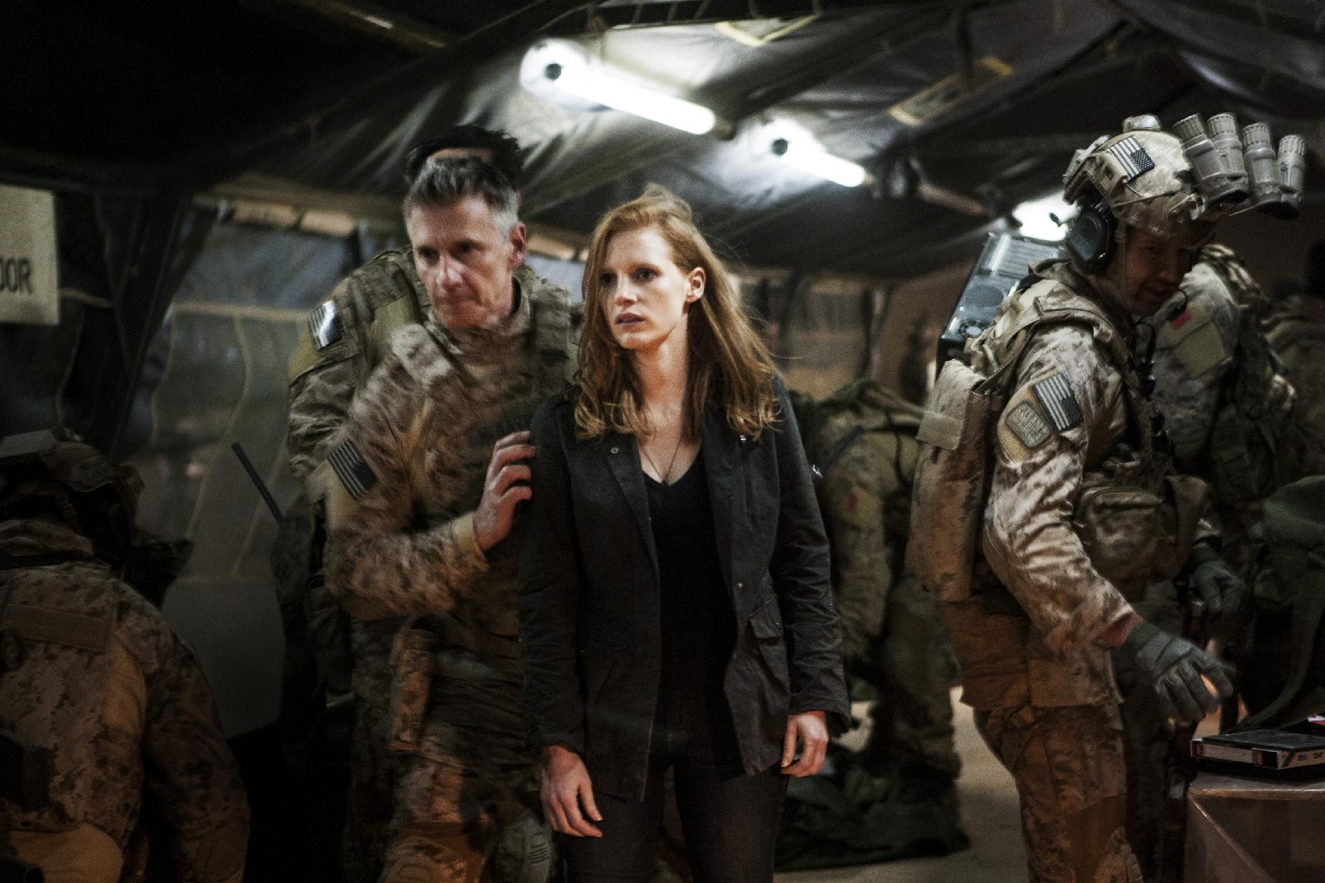 In this undated publicity photo released by Columbia Pictures Industries, Inc., Jessica Chastain, center, plays a member of the elite team of spies and military operatives, stationed in a covert base overseas, with Christopher Stanley, left, and Alex Corbet Burcher, right, who secretly devote themselves to finding Osama Bin Laden in Columbia Pictures' new thriller,