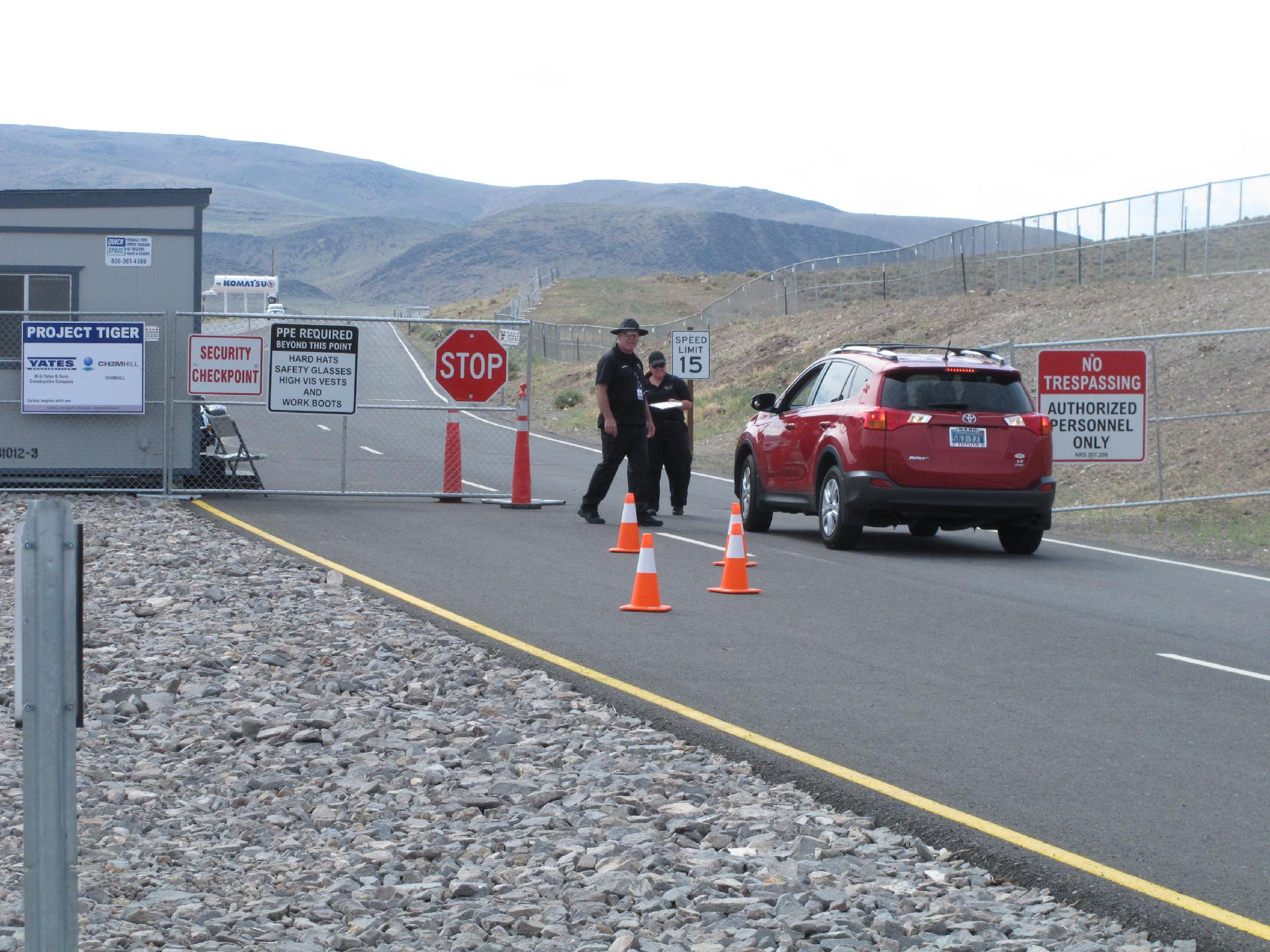 """Security guards stop a car Friday Aug. 1, 2014, at the gate to the site Tahoe Reno Industrial Center about 15 miles east of Reno, Nevada where Tesla Motors has broken ground as one of the possible places to build a $5 billion """"gigafactory'' to make lithium batteries for its electric cars. (AP Photo/Scott Sonner)"""