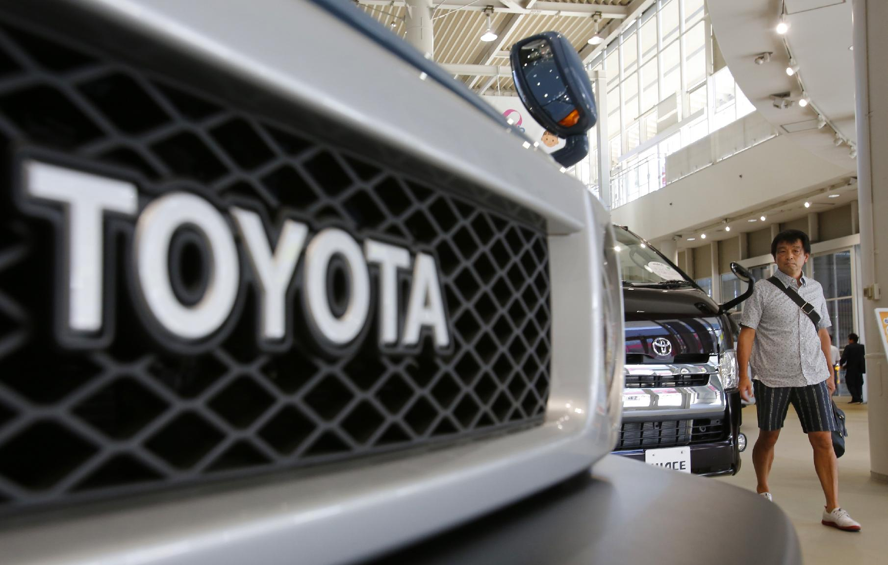 A visitor walks around a Toyota showroom in Tokyo, Tuesday, Aug. 5, 2014. Toyota Motor Corp. reported a better-than-expected rise in quarterly profit as vehicle sales grew in North America and Europe, offsetting a drop in Japan. (AP Photo/Shizuo Kambayashi)