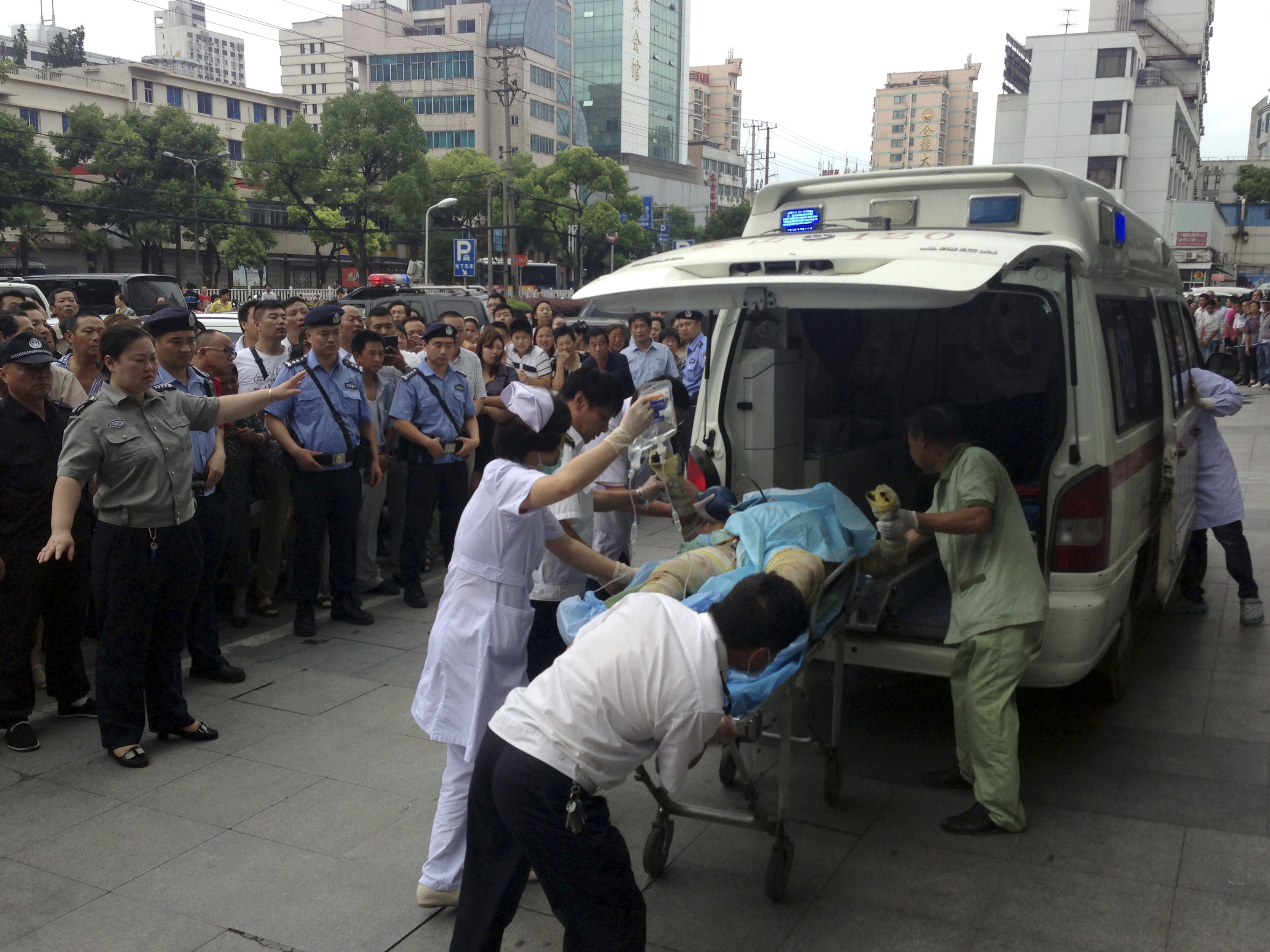 Medical staff move a severely burnt victim of an explosion at an eastern Chinese automotive parts factory