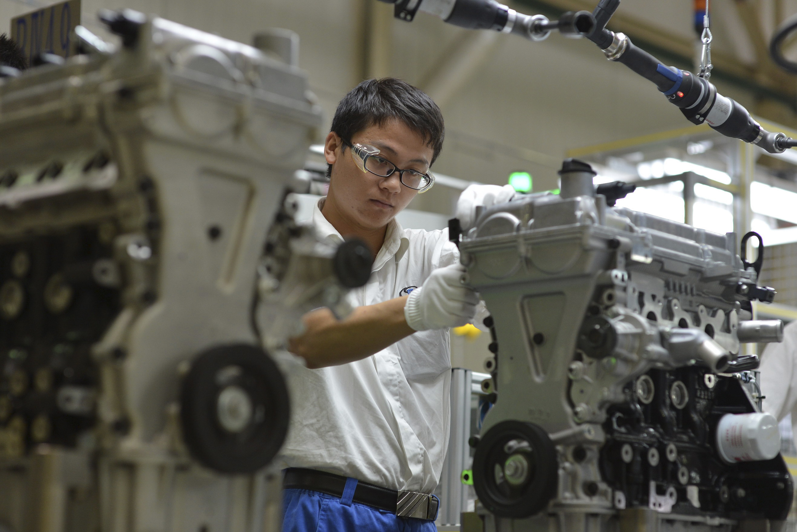 In this Tuesday, Sept. 23, 2014 photo, a worker assembles engines at the General Motors engine plant in Wuhan in central China's Hubei province. General Motors Co. expects its sales in China this year to top 3.1 million units and sees no impact on business from an anti-monopoly probe of the industry, the automaker's China unit President Matt Tsien said Wednesday, Sept. 24, 2014. (AP Photo) CHINA OUT