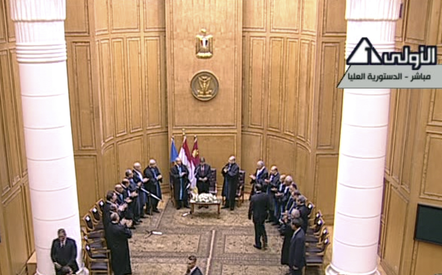 In this image made from Egyptian State Television, judges from Egypt's Supreme constitutional court applaud Mohammed Morsi, center, after he was sworn in as President in Cairo, Egypt, Saturday, June 30, 2012. Islamist Mohammed Morsi has been sworn in before Egypt's highest court as the country's first freely elected president, succeeding Hosni Mubarak who was ousted 16 months ago.(AP Photo/Egyptian State TV)