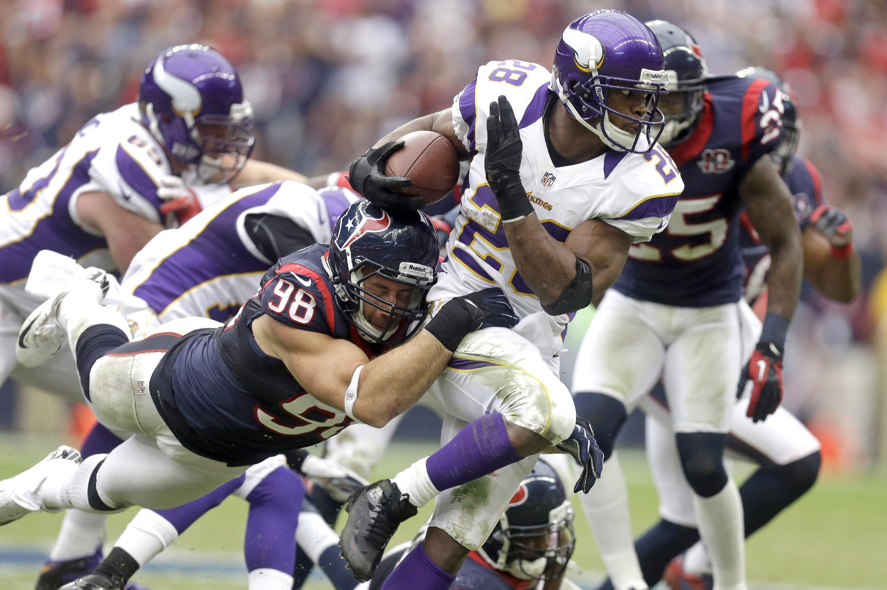 Adrian Peterson (28) tries to turn upfield as Houston Connor Barwin (98) latches on to him. (AP)