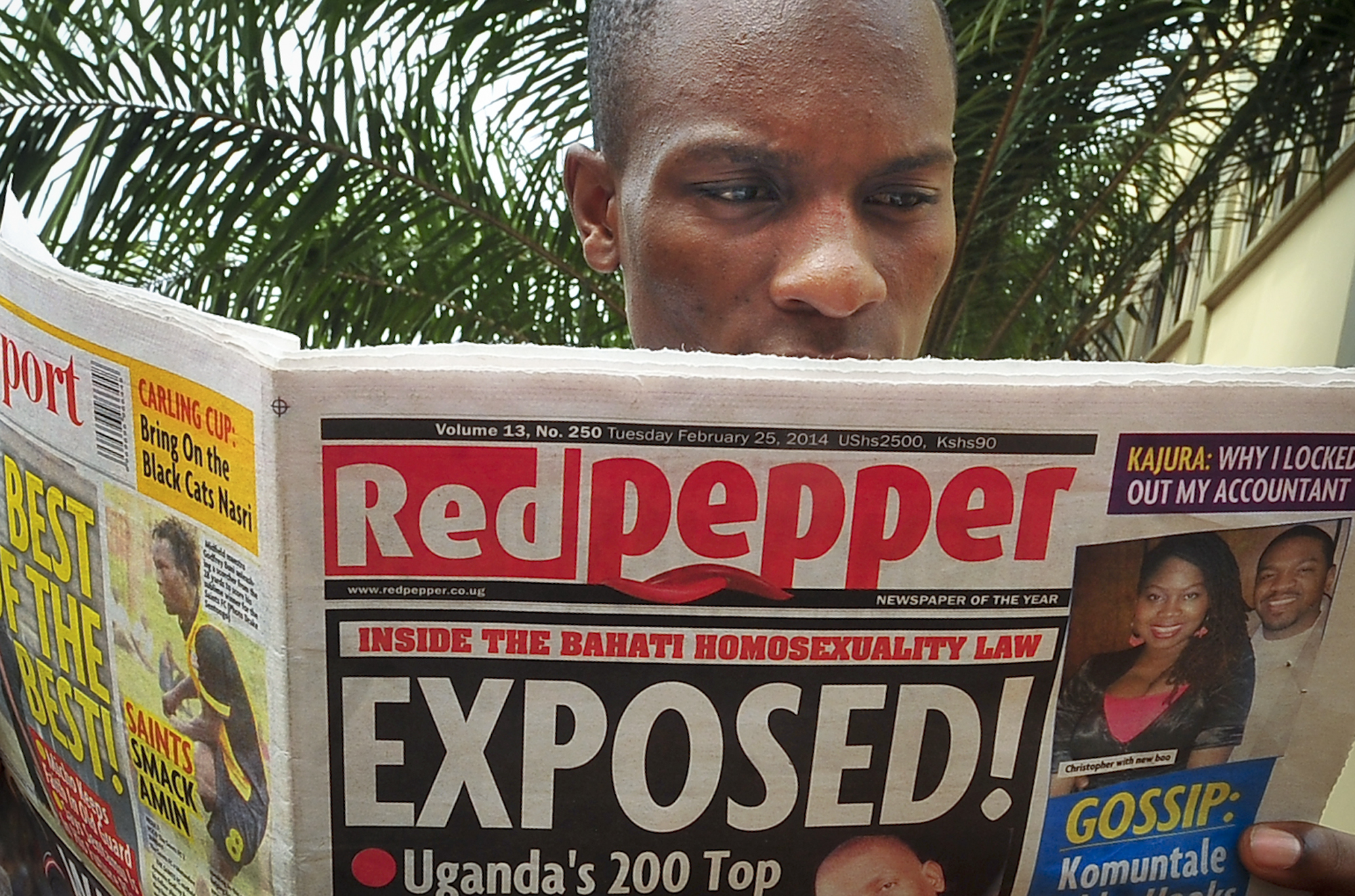 """A Ugandan reads a copy of the """"Red Pepper"""" tabloid newspaper in Kampala, Uganda Tuesday, Feb. 25, 2014. The Ugandan newspaper published a list Tuesday of what it called the country's """"200 top"""" homosexuals, outing some Ugandans who previously had not identified themselves as gay, one day after the president Yoweri Museveni enacted a harsh anti-gay law. (AP Photo/Stephen Wandera)"""