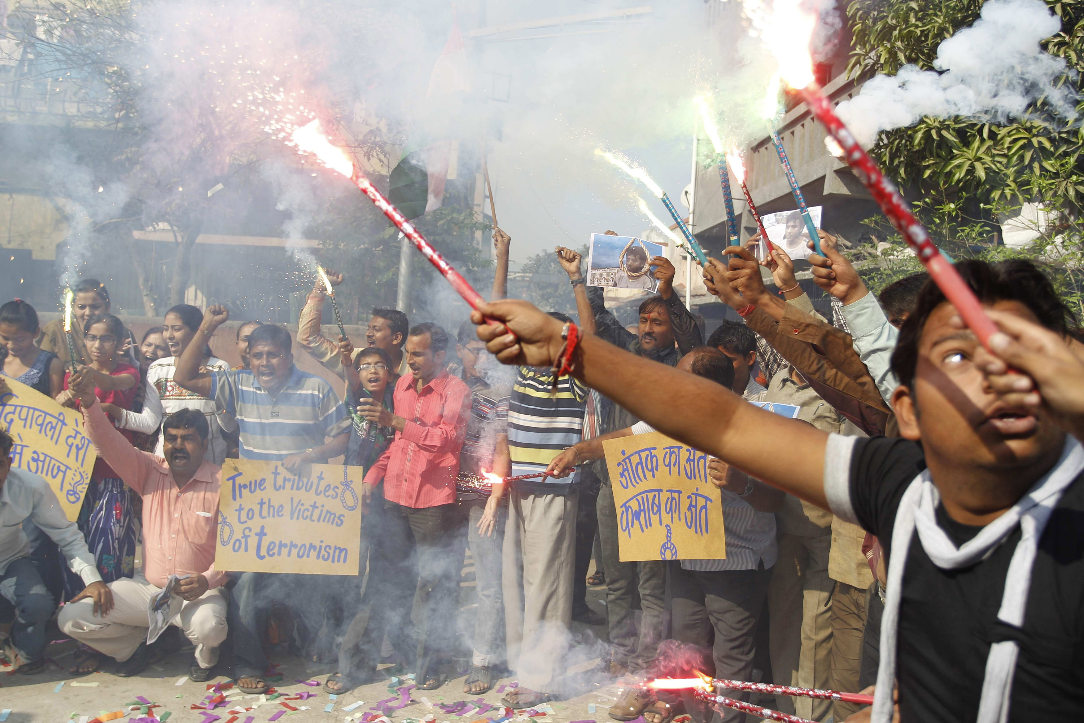Indians celebrate upon hearing the news of India executing Mohammed Ajmal Kasab, the lone surviving gunman from the 2008 terror attacks, in Ahmadabad, India, Wednesday, Nov. 21, 2012. Kasab, a Pakistani citizen, was one of 10 gunmen who rampaged through the streets of India's financial capital for three days in November 2008, killing 166 people. Kasab was hung in secrecy at 7:30 a.m. Wednesday at a jail in Pune, a city near Mumbai, after Indian President Pranab Mukherjee rejected his plea for mercy. (AP Photo/Ajit Solanki)