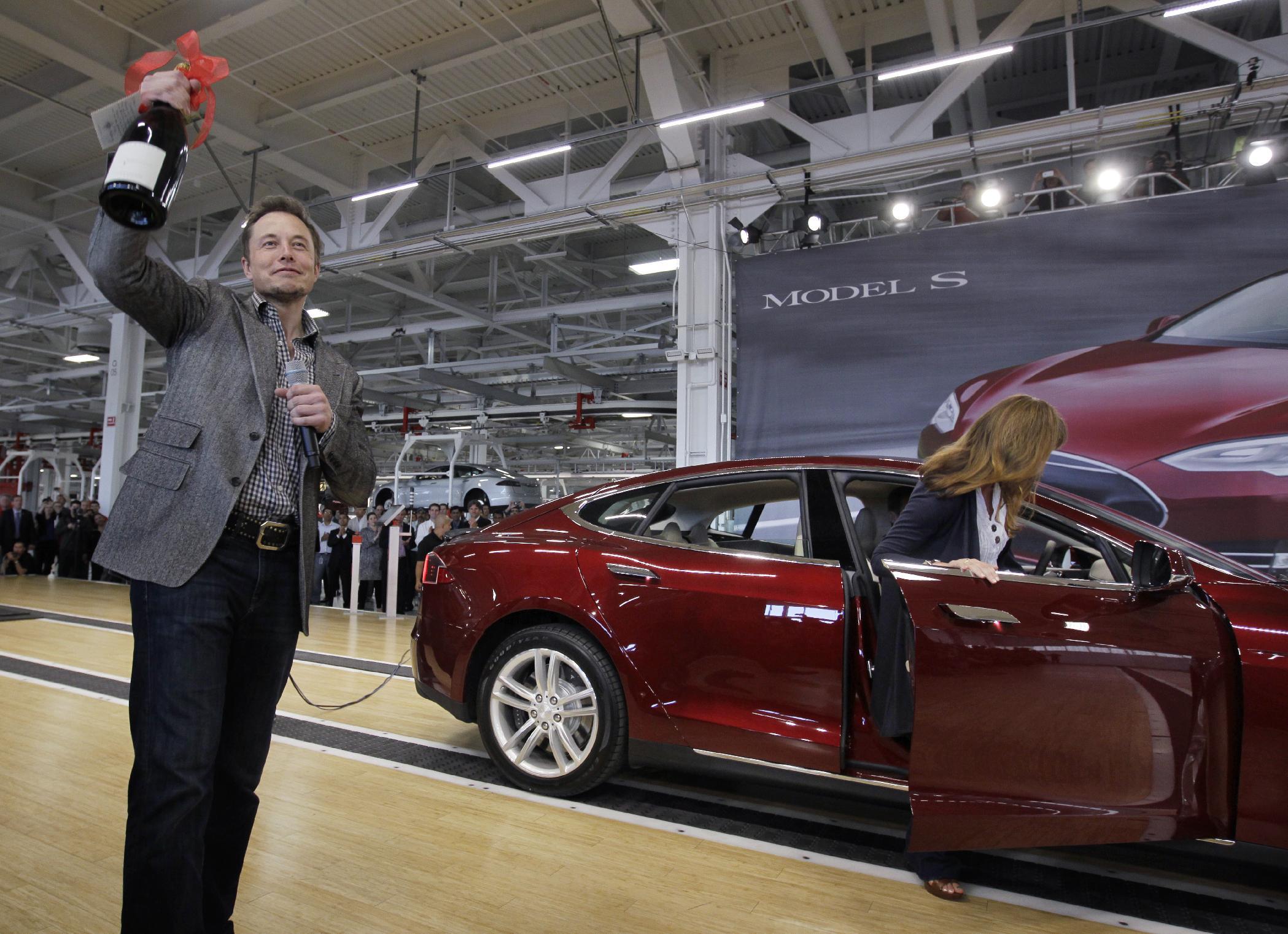 Tesla Motors Inc. CEO Elon Musk holds up a bottle of wine