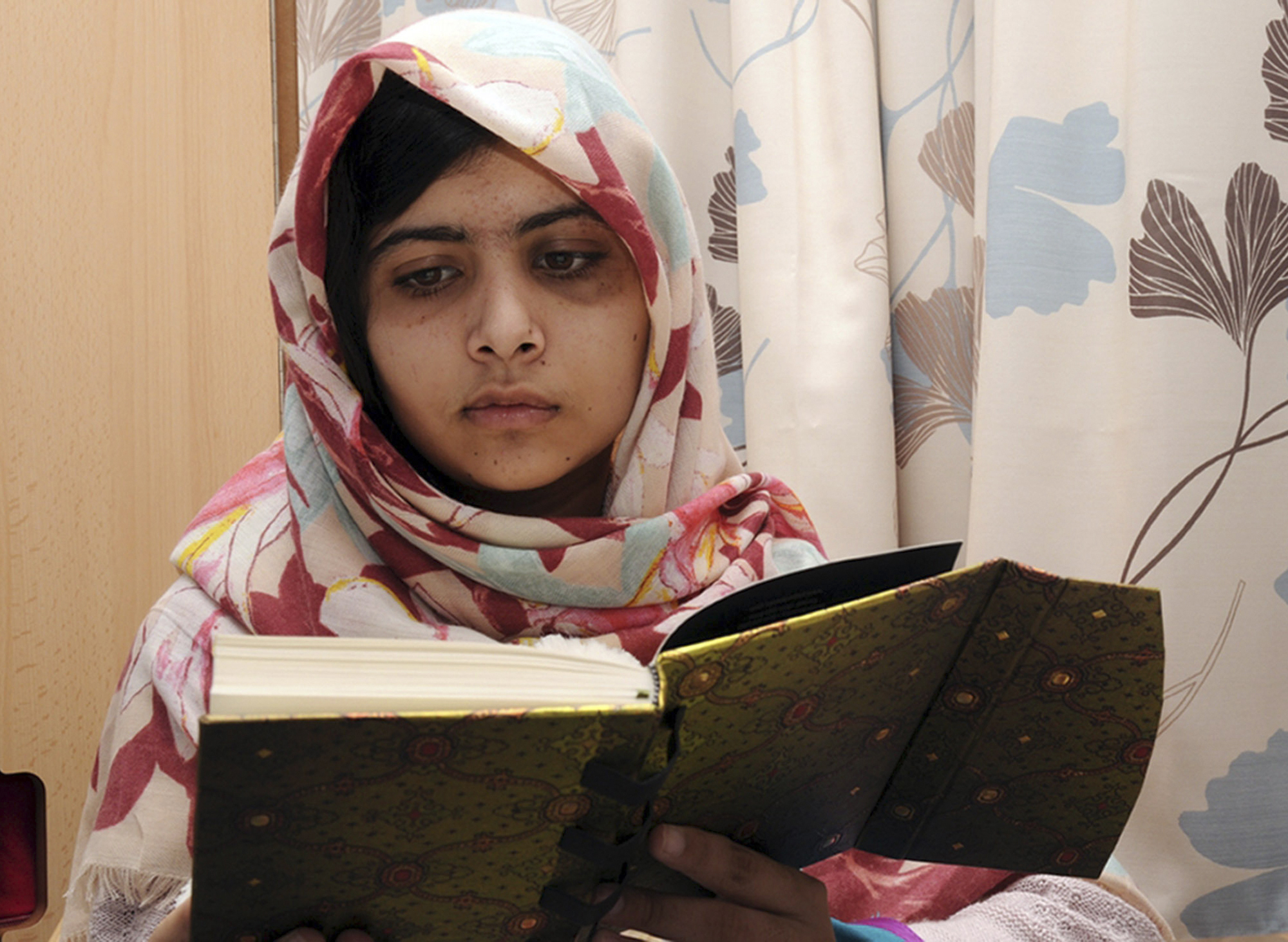 """FILE - In this undated file photo provided by Queen Elizabeth Hospital in Birmingham, England, Malala Yousufzai, the 15-year-old girl who was shot at close range in the head by a Taliban gunman in Pakistan, reads a book as she continues her recovery at the hospital. Malala Yousafzai, the Pakistani teenager shot in the head by the Taliban, is writing a memoir. Publisher Weidenfeld and Nicolson said Thursday March 28, 2013 it will release """"I am Malala"""" in Britain this fall. Little, Brown will publish it in the United States.A Taliban gunman shot Malala on Oct. 9, while she was on her way home from school in northwestern Pakistan. (AP Photo/Queen Elizabeth Hospital, File)"""
