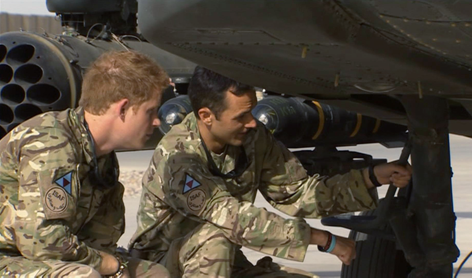 In this image from video, Britain's Prince Harry, left, has a close look at an Apache helicopter, during a tour with a member of his squadron, (name not provided) at Camp Bastion in Afghanistan, Friday Sept. 7, 2012. Prince Harry will be based at Camp Bastion during his tour of duty as a co-pilot gunner, returning to Afghanistan to fly attack helicopters in the fight against the Taliban. (AP Photo/TV Pool)