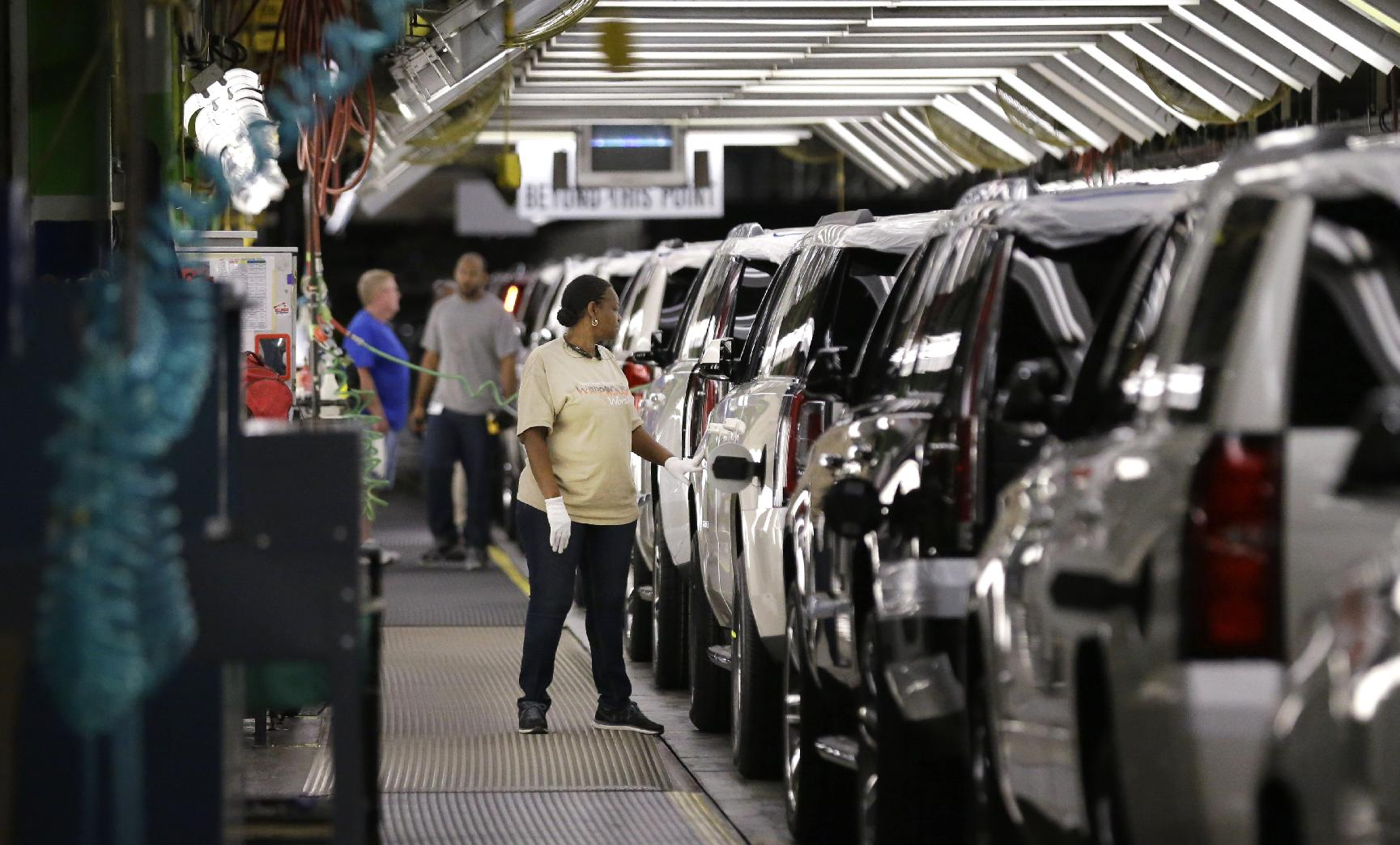 FILE - In this May 13, 2014 file photo, an auto worker inspects finished SUVs coming off the assembly line at the General Motors auto plant in Arlington, Texas. As General Motors tackles a safety crisis, a look at its numbers from June show just how intent the company is on keeping new-car sales on the rise during a record spate of safety recalls. (AP Photo/LM Otero, File)