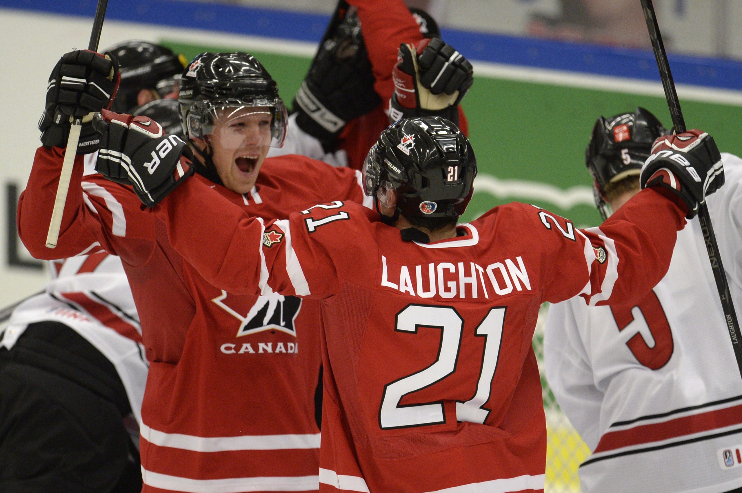 Canada's Griffin Reinhart, left, and Scott Laughton (21) celebrate Canada's first goal during first period action in a quarterfinal match at the world junior hockey tournament in Malmo, Sweden, Thursday, Jan 2, 2014. (AP Photo/The Canadian Press, Frank Gunn)