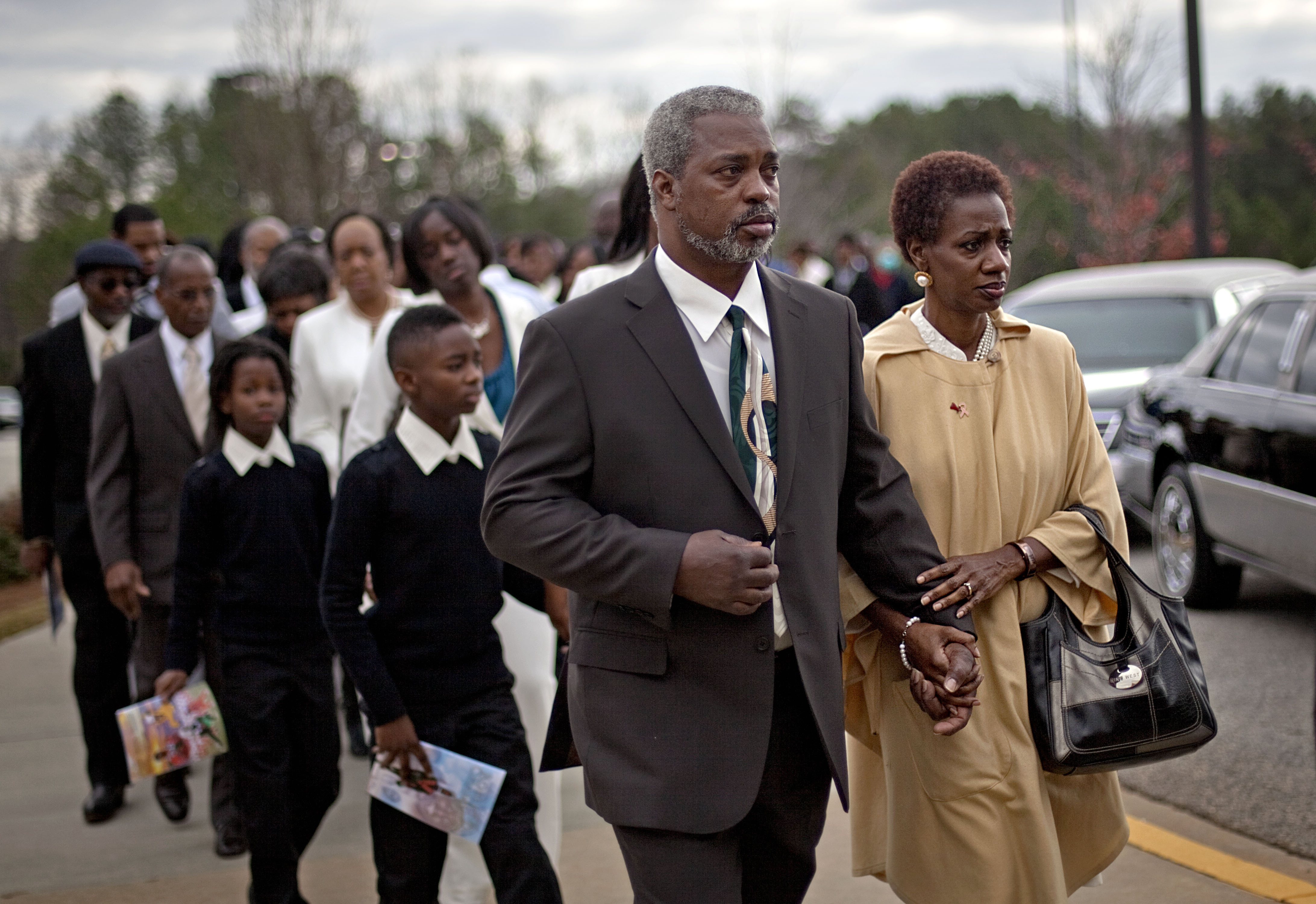 FILE -In this Wednesday, Nov. 30, 2011 file photo, Robert Champion Sr., left, and his wife, Pam lead a procession into the funeral service for their son, Florida A&M University band member Robert Champion, in Decatur, Ga. The parents of a slain Florida A&M University drum major are concerned because the investigation into his hazing death three months ago in Orlando has not produced any arrests. The attorney for Robert Champion Sr. and Pamela Champion says they're worried because charges have been filed in two other FAMU band hazing cases that were less serious. (AP Photo/David Goldman, File)