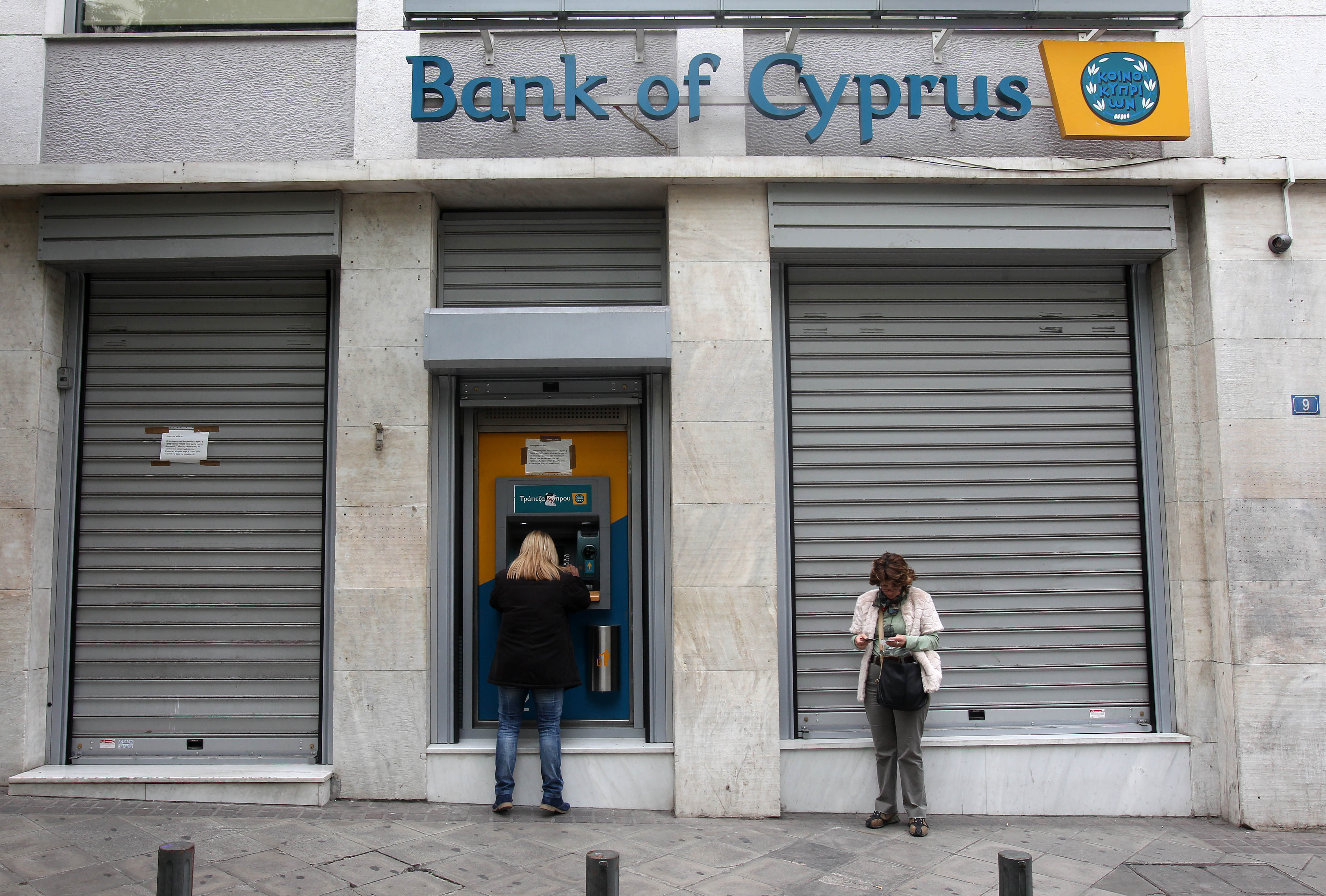 Customers of Bank of Cyprus use the ATM. (AP Photo/Thanassis Stavrakis)