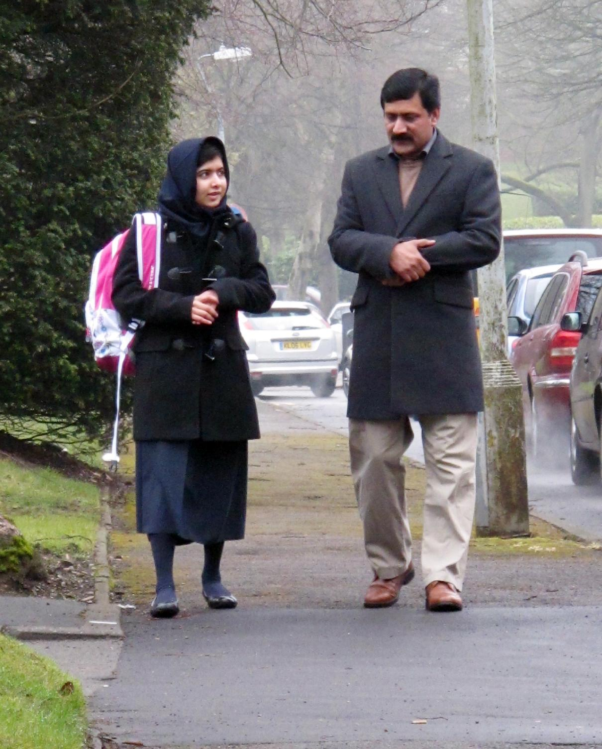 Image made available by her press office of Malala Yousafzai, the Pakistani schoolgirl shot in the head by the Taliban, with her father Ziauddin, as she attends her first day of school on Tuesday March 19, 2013 just weeks after being released from hospital. The 15-year-old participated in lessons at the Edgbaston High School for Girls in Birmingham. She survived an assassination attempt by the fundamentalist political group in October last year and underwent hours of surgery in the UK to try and repair the damage caused by a bullet which grazed her brain. (AP Photo/ Malala Press Office)