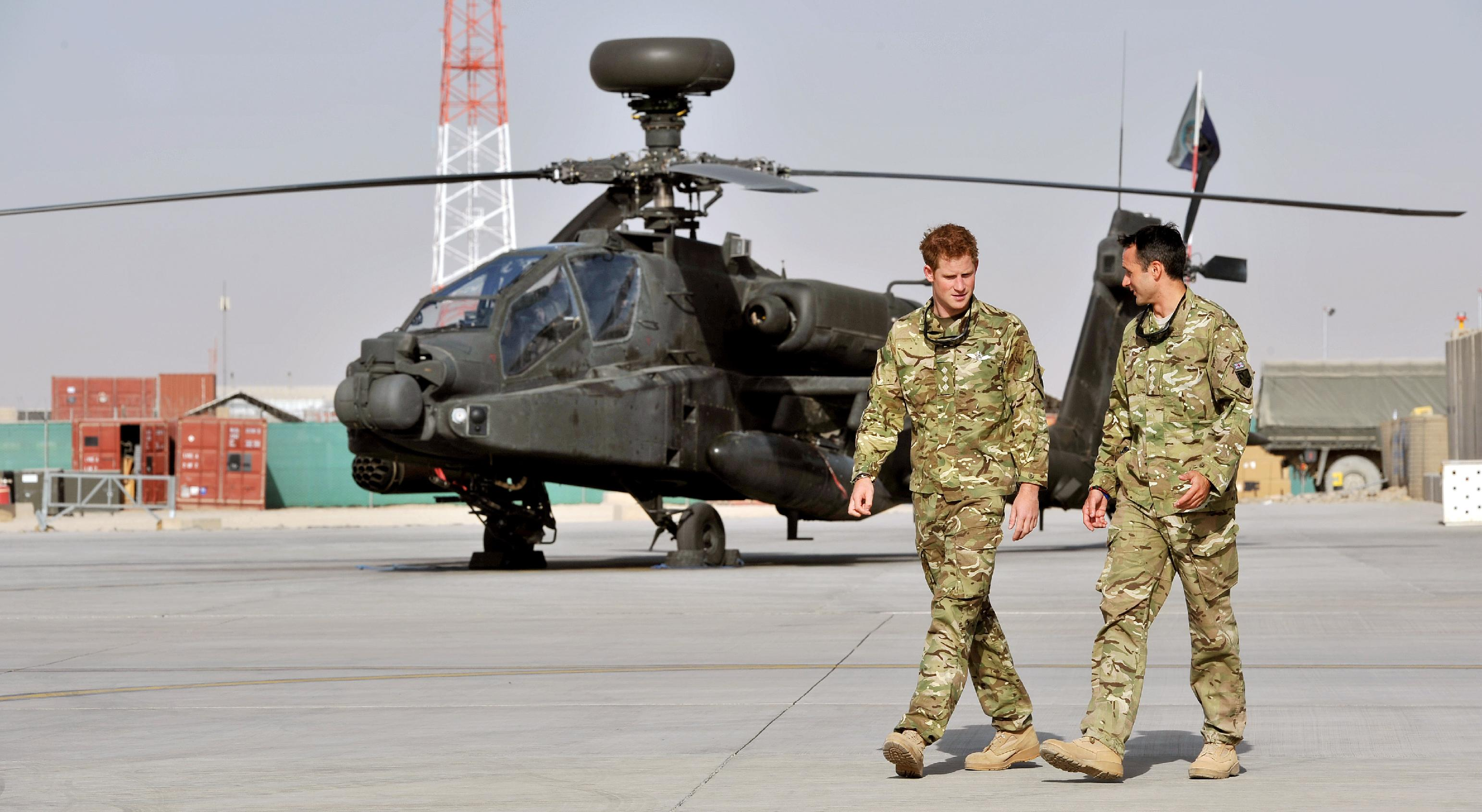 Britain's Prince Harry is shown the Apache flight-line Friday Sept 7 2012 by a member of his squadron (name not provided) at Camp Bastion in Afghanistan, where he will be operating from during his tour of duty as a co-pilot gunner. The Prince has returned to Afghanistan to fly attack helicopters in the fight against the Taliban. (AP Photo/ John Stillwell, Pool)