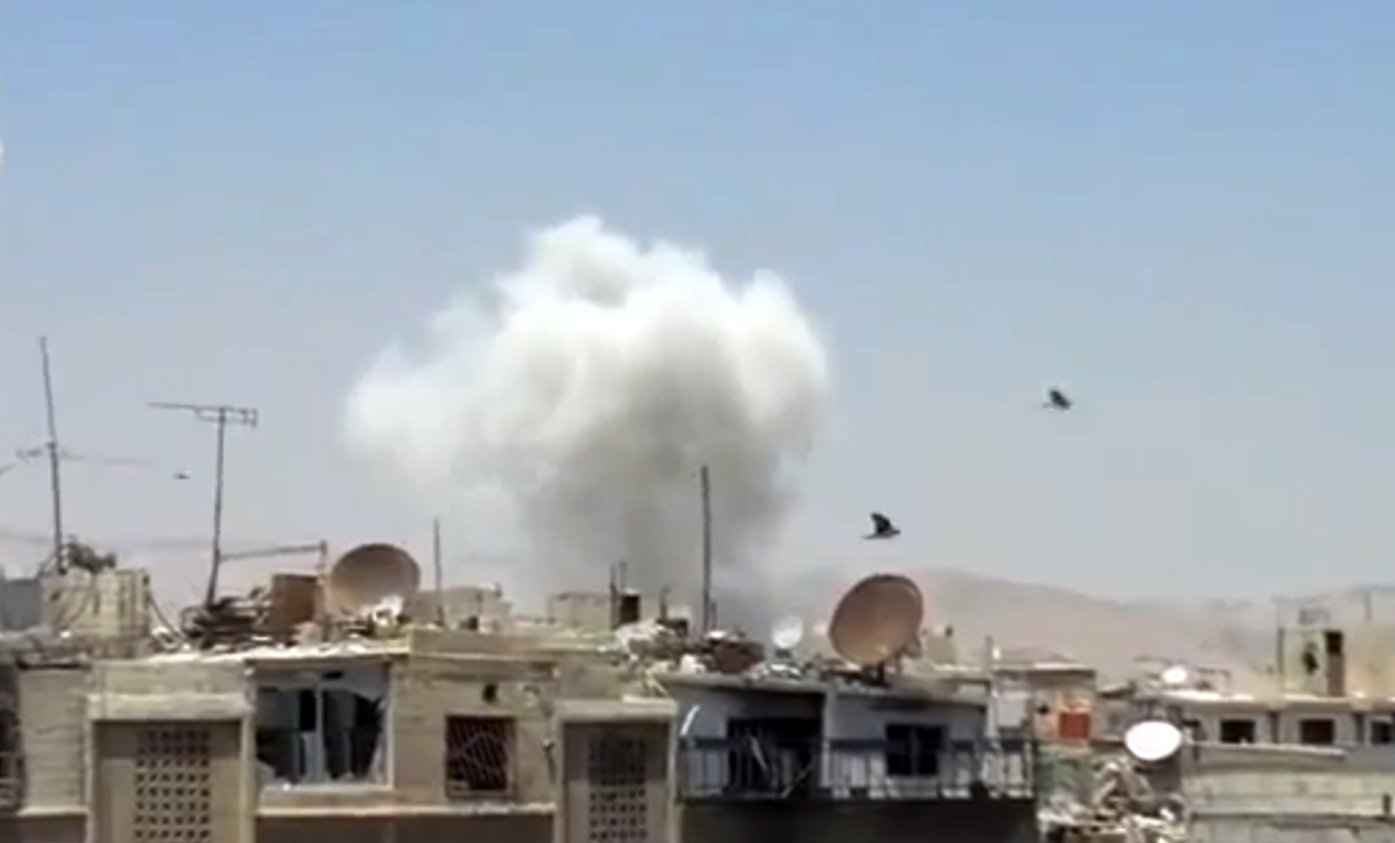 In this image taken from video obtained from the Shaam News Network, which has been authenticated based on its contents and other AP reporting, columns of smoke billow above houses as a result of heavy bombing in Damascus, Syria, Monday July 22, 2013. Syrian rebels seized a strategic village on the edge of the northern city of Aleppo on Monday, activists said, just hours after other opposition fighters sustained some of their heaviest losses in months in battles to the south near the capital, Damascus. (AP Photo/Shaam News Network via AP video)