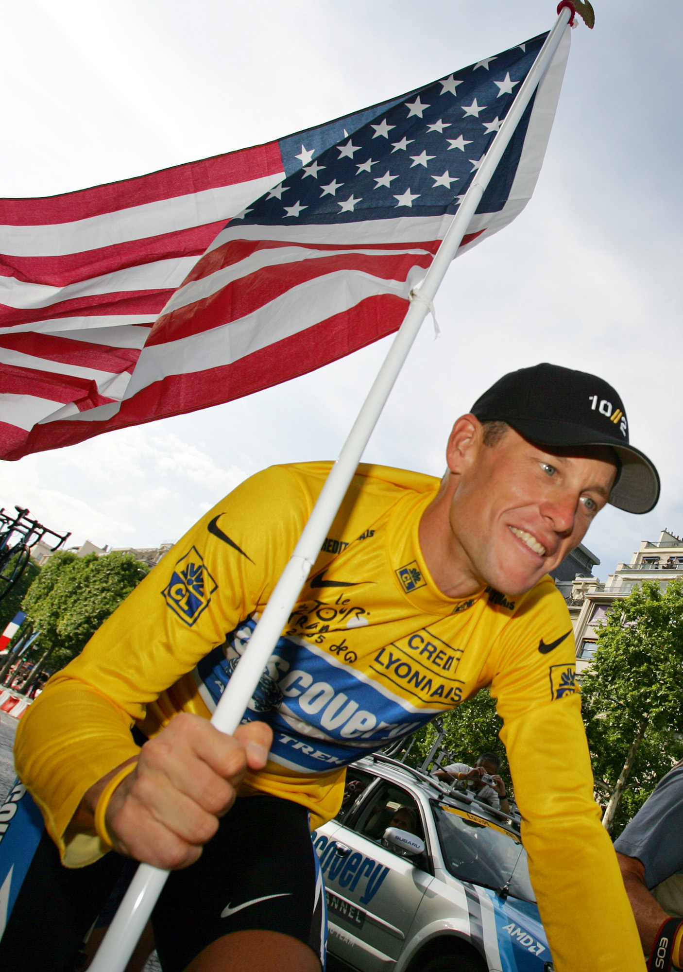 Lance Armstrong carries the U.S. flag during a victory parade after winning his seventh Tour de France. (AP)