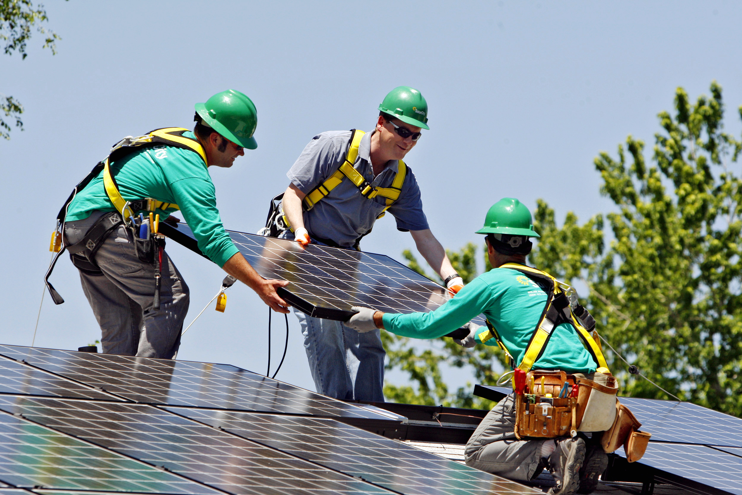 FILE - In this June 18, 2010, file photo, U.S. Senator Michael Bennet, D-Colo., center, helps as SolarCity employees Jarret Esposito, left, and Jake Torwatzky, install a solar panel on a home in south Denver. SolarCity, one of the nation's largest installers of rooftop solar systems, on Tuesday, June 17, 2014 announced it is buying Silveo, a solar panel manufacturer. (AP Photo/Ed Andrieski, File)