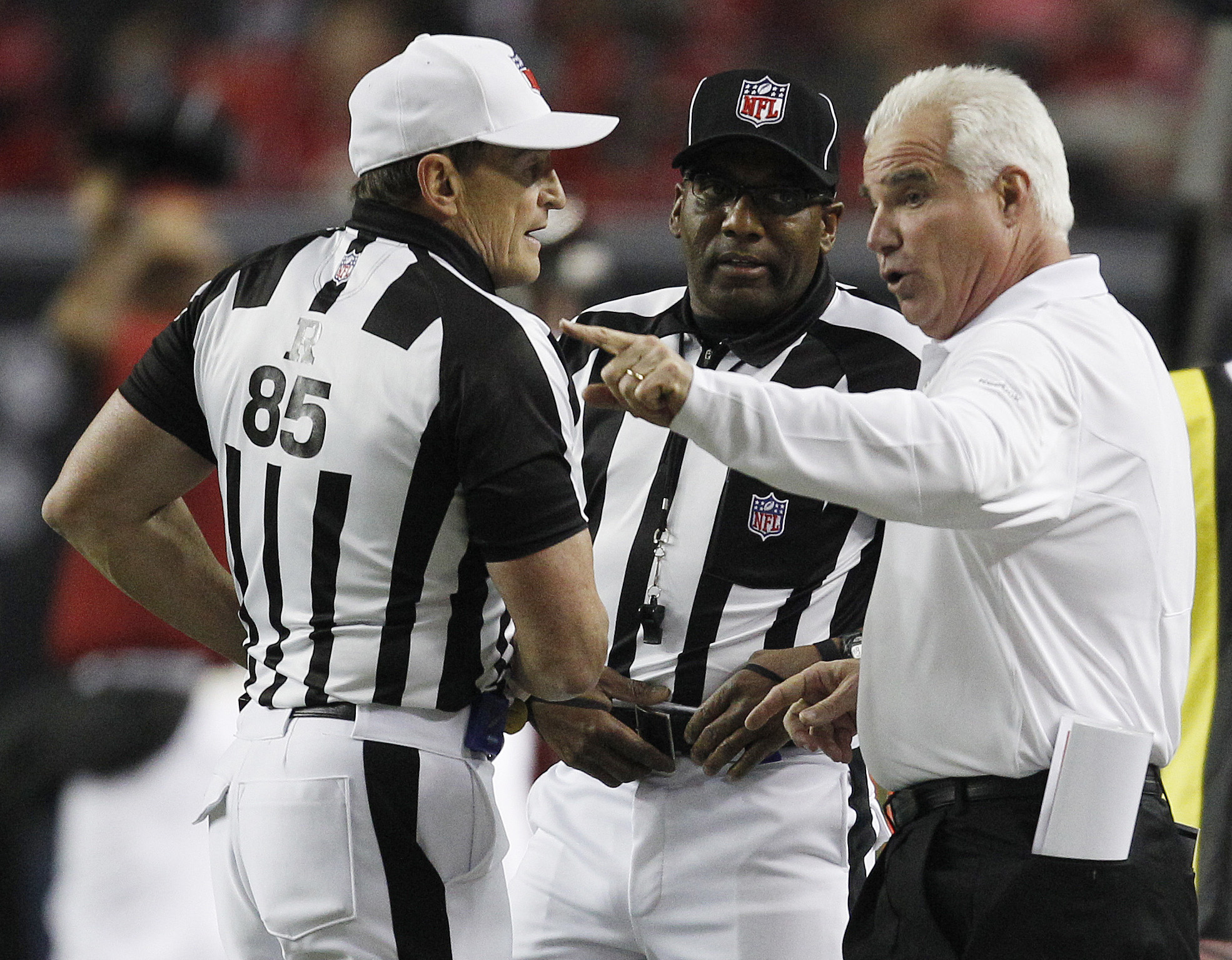 Referee Ed Hochuli (85) dispenses justice with Falcons coach Mike Smith during a game. (AP)