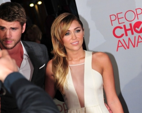 Liam Hemsworth and Miley Cyrus being photographed at the 2012 People's Choice Awards.