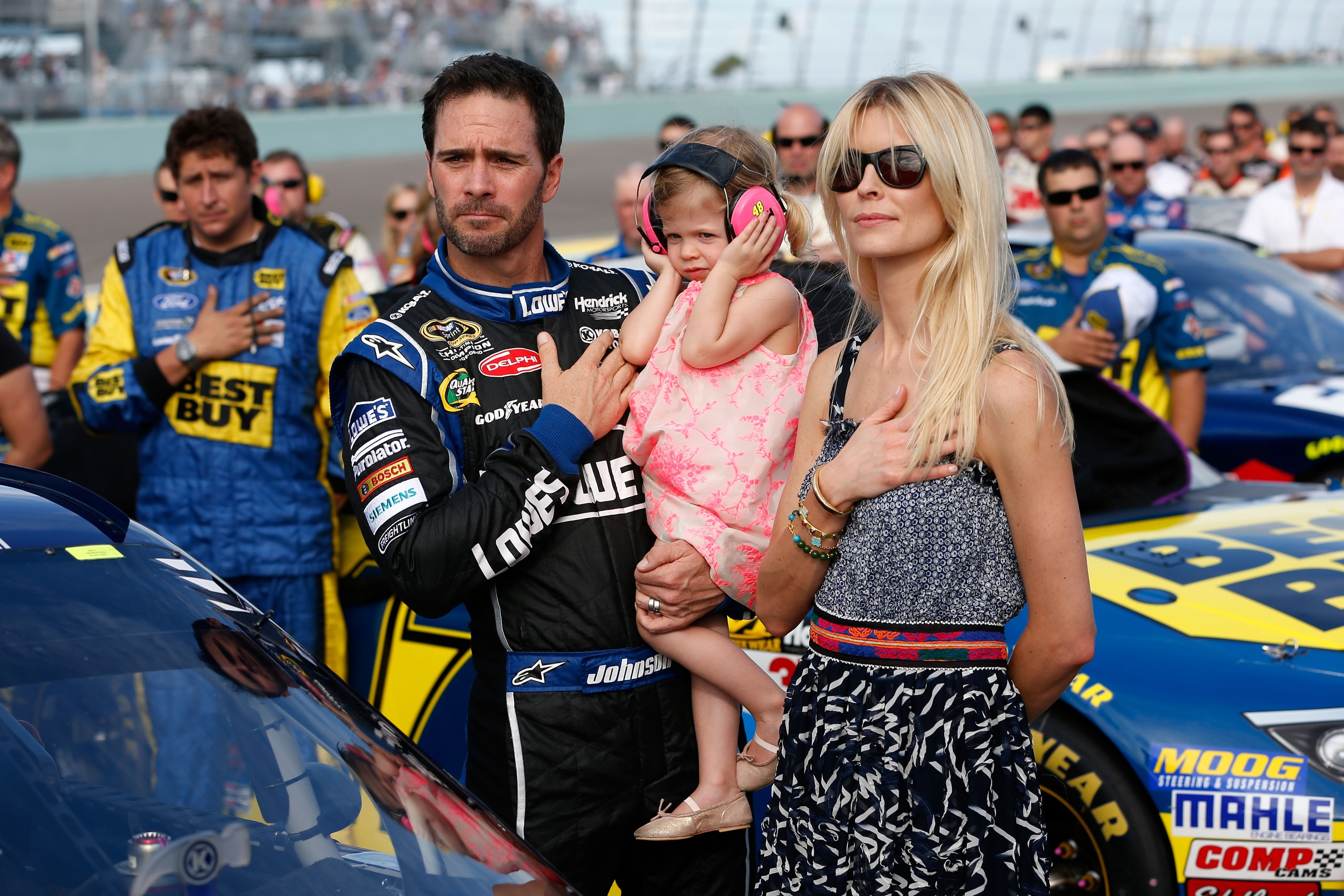 Jimmie Johnson holds his daughter Evie while standing with wife Chandra. (Getty Images)