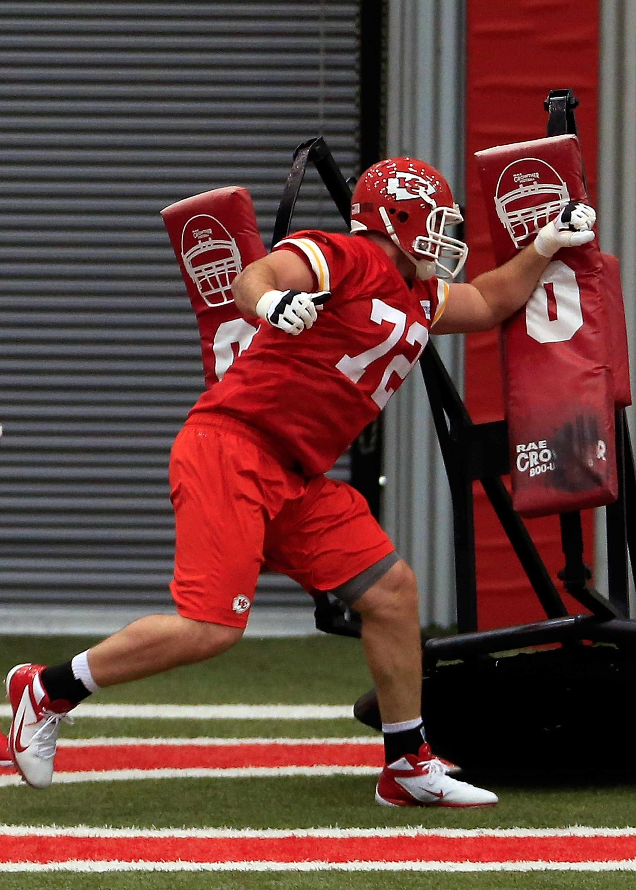 Eric Fisher hits a tackling dummy while practicing at Chiefs rookie camp. (Getty)