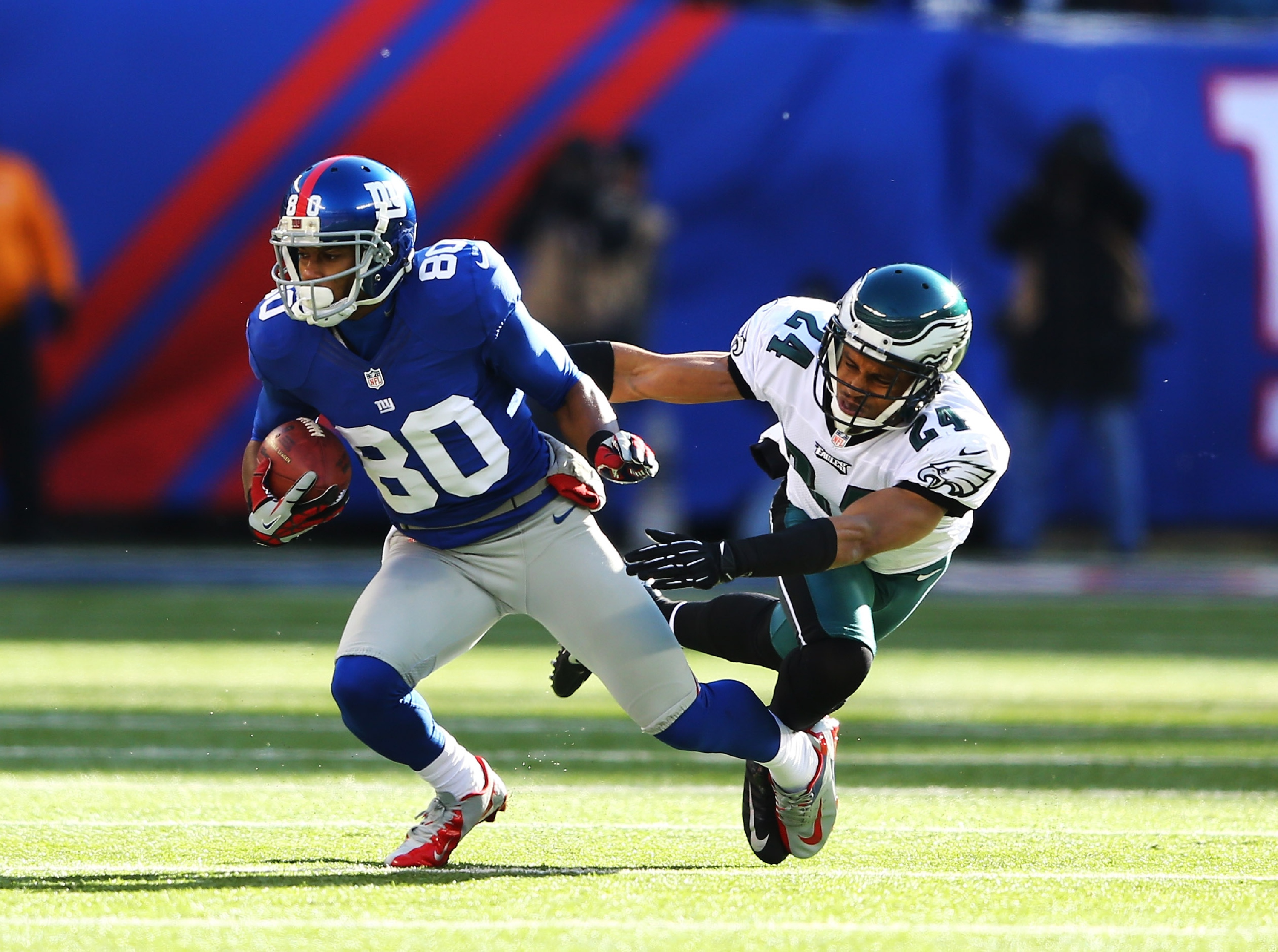 Victor Cruz runs away from Eagles CB Nnamdi Asomugha in 2012. (Getty)