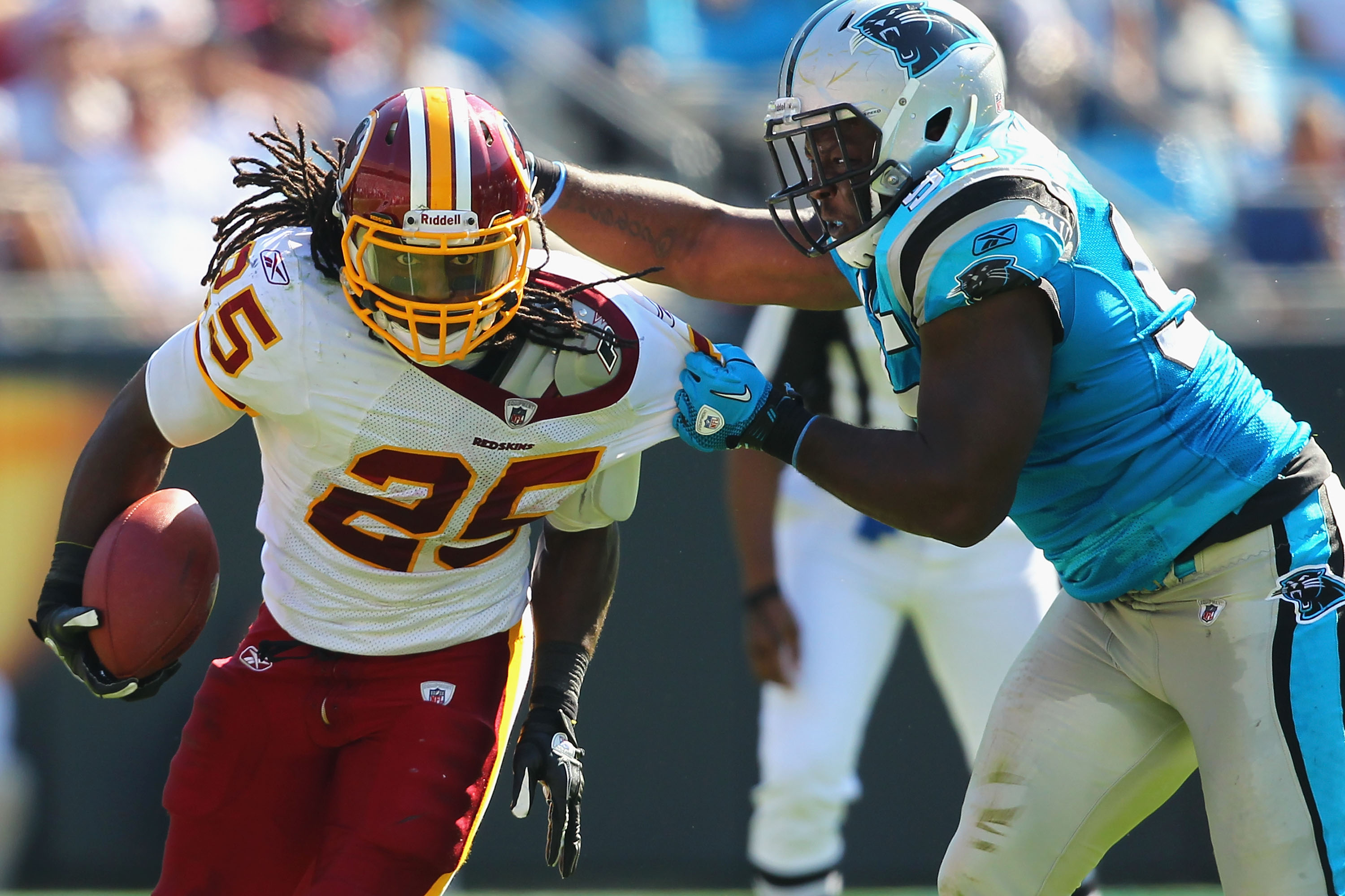 Tim Hightower is tackled by Panthers DL Charles Johnson last season. (Getty Images)