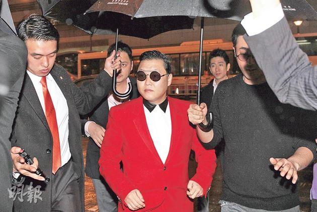 昨晚換上一身紅衣的Psy,在多名保安擔遮擋雨下落遊艇遊維港。(攝影﹕劉永銳、李維隆)