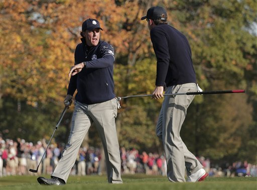 Phil Mickelson, left, is congratulated by Keegan Bradley after making a putt on the fifth hole. (AP)